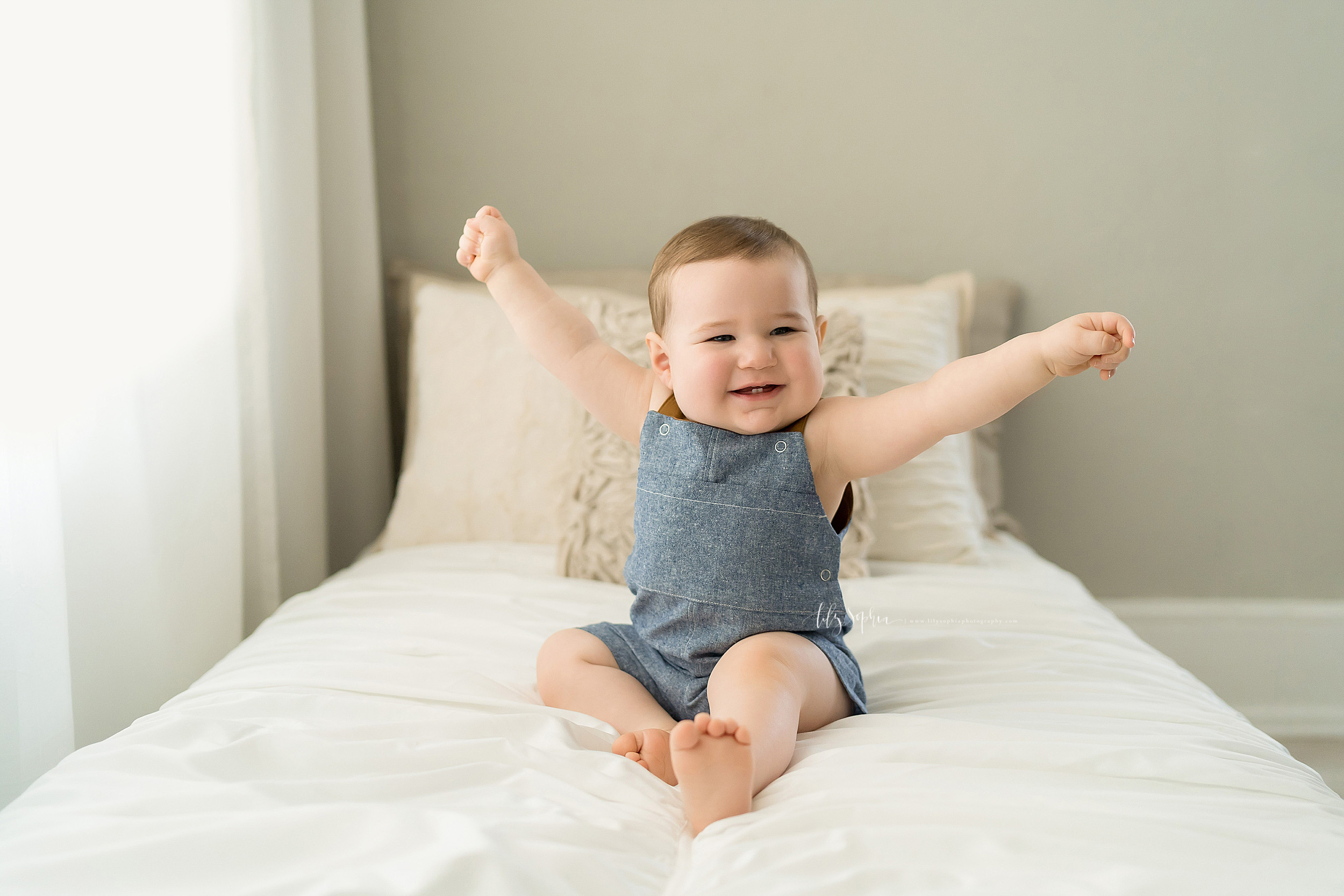 Photo of a proud one year old boy sitting on a bed in a studio in Atlanta wearing a denim one piece outfit and holding his hands in the air to show how big he is taken in natural light.