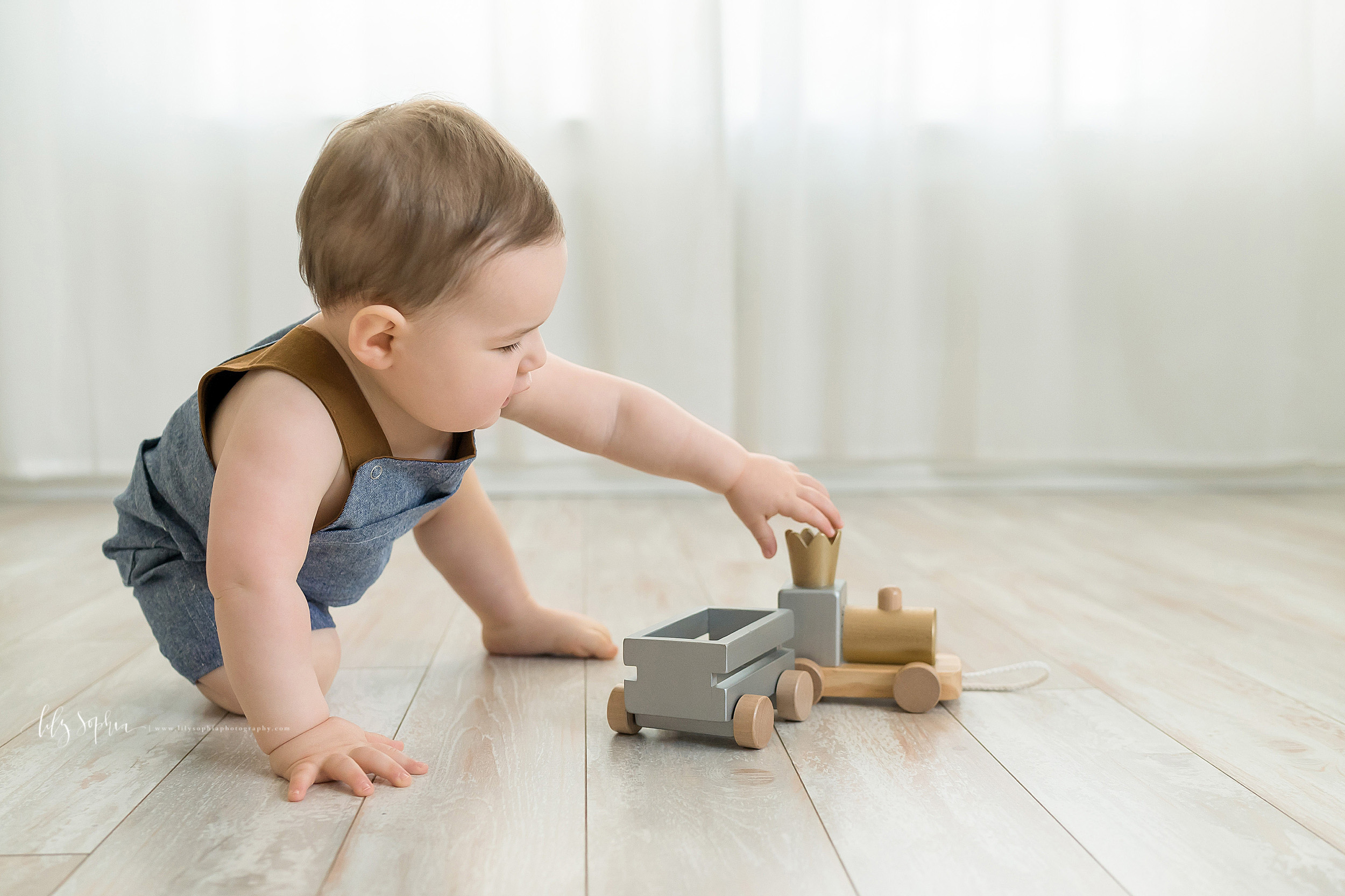 Milestone photo of a one year old little boy as he plays with a wooden train on the floor of a natural light Atlanta studio.
