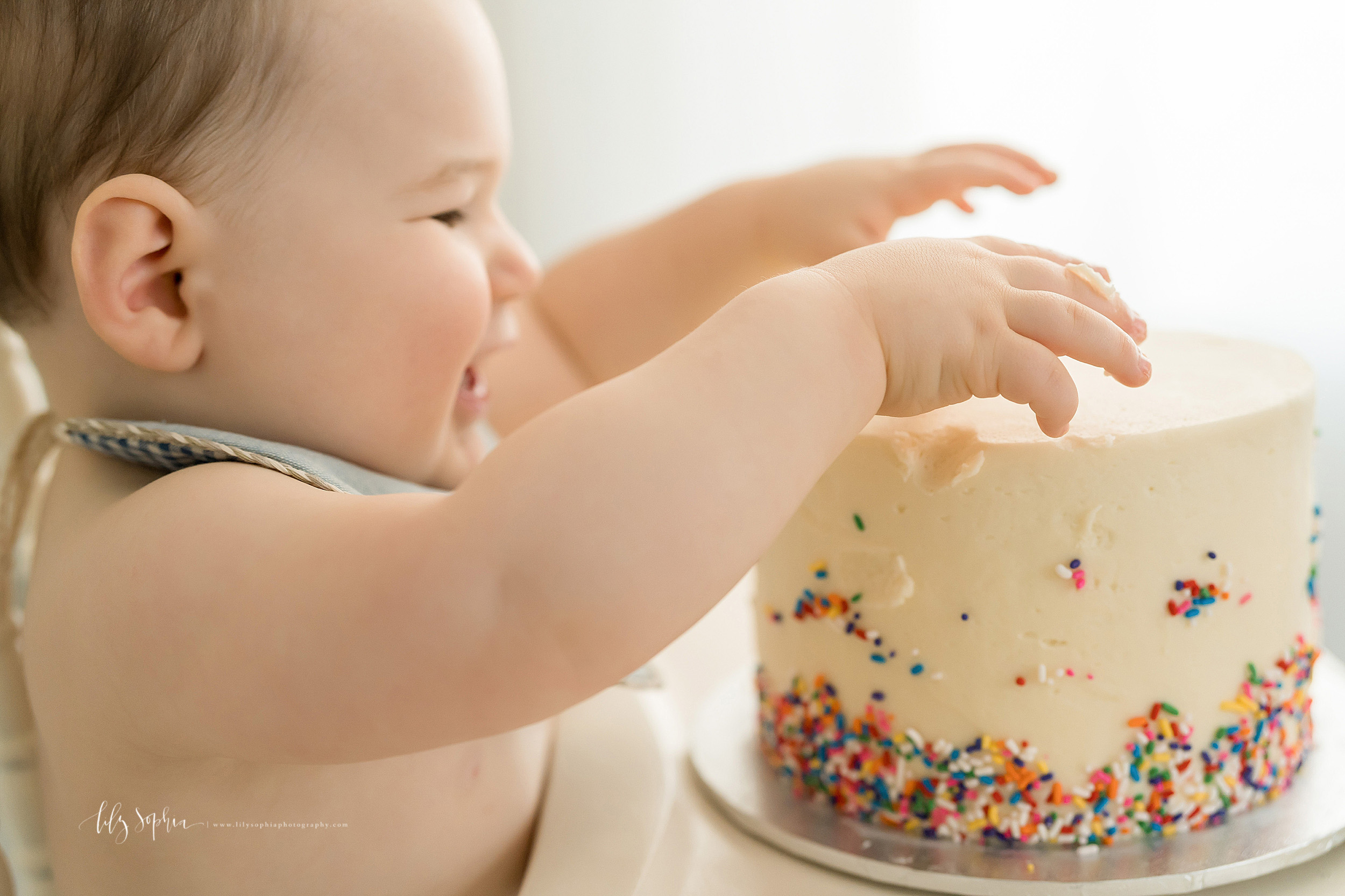 Photo of a one year old boy who is ready to dig into his birthday cake as he sits in an antique highchair in natural light in a studio in Atlanta.