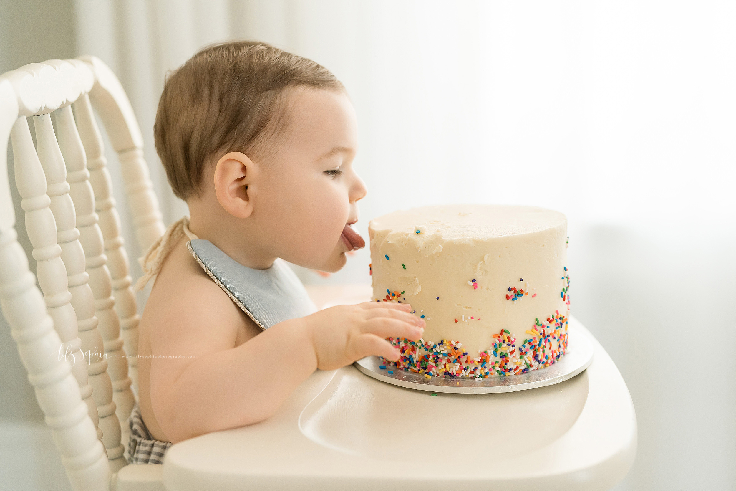 Milestone photo of a one year old boy sitting in an antique high chair in an Atlanta natural light studio as he sticks his tongue out to taste his birthday cake.