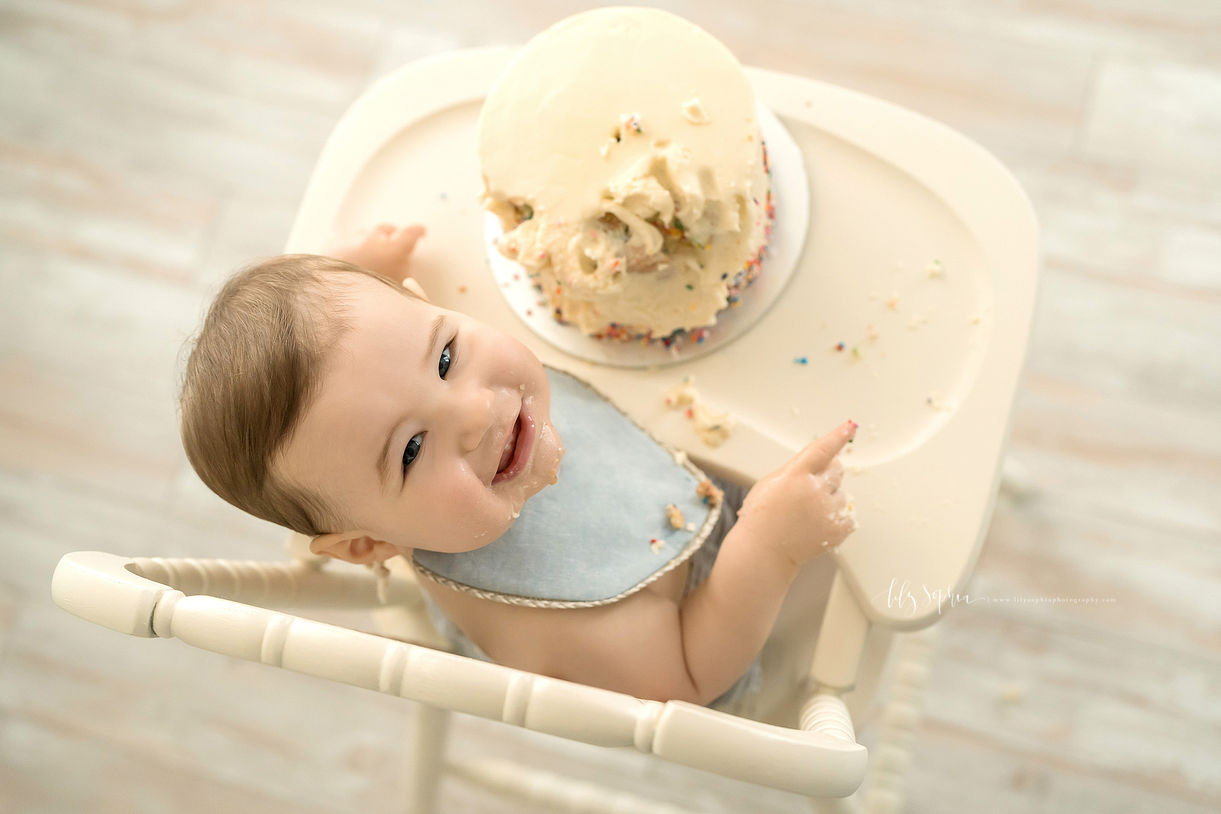 Overhead milestone shot of a one year old little boy  who has dug into his birthday cake and is proudly displaying the proof of it as he sits in an antique highchair in natural light in a studio in Atlanta.
