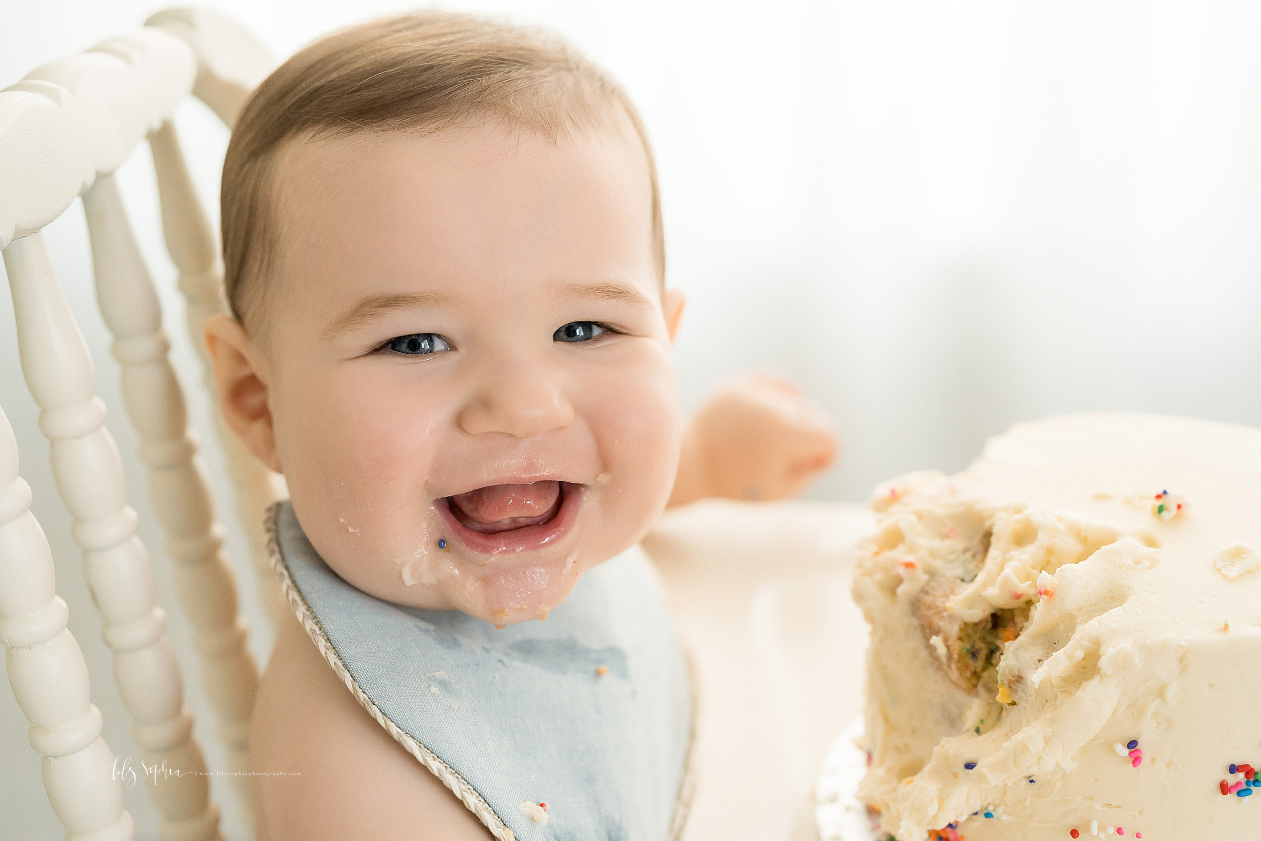 Milestone photo of a bright-eyed one year old boy with icing all over his face as he sits in a highchair with his birthday cake in Atlanta, Georgia.