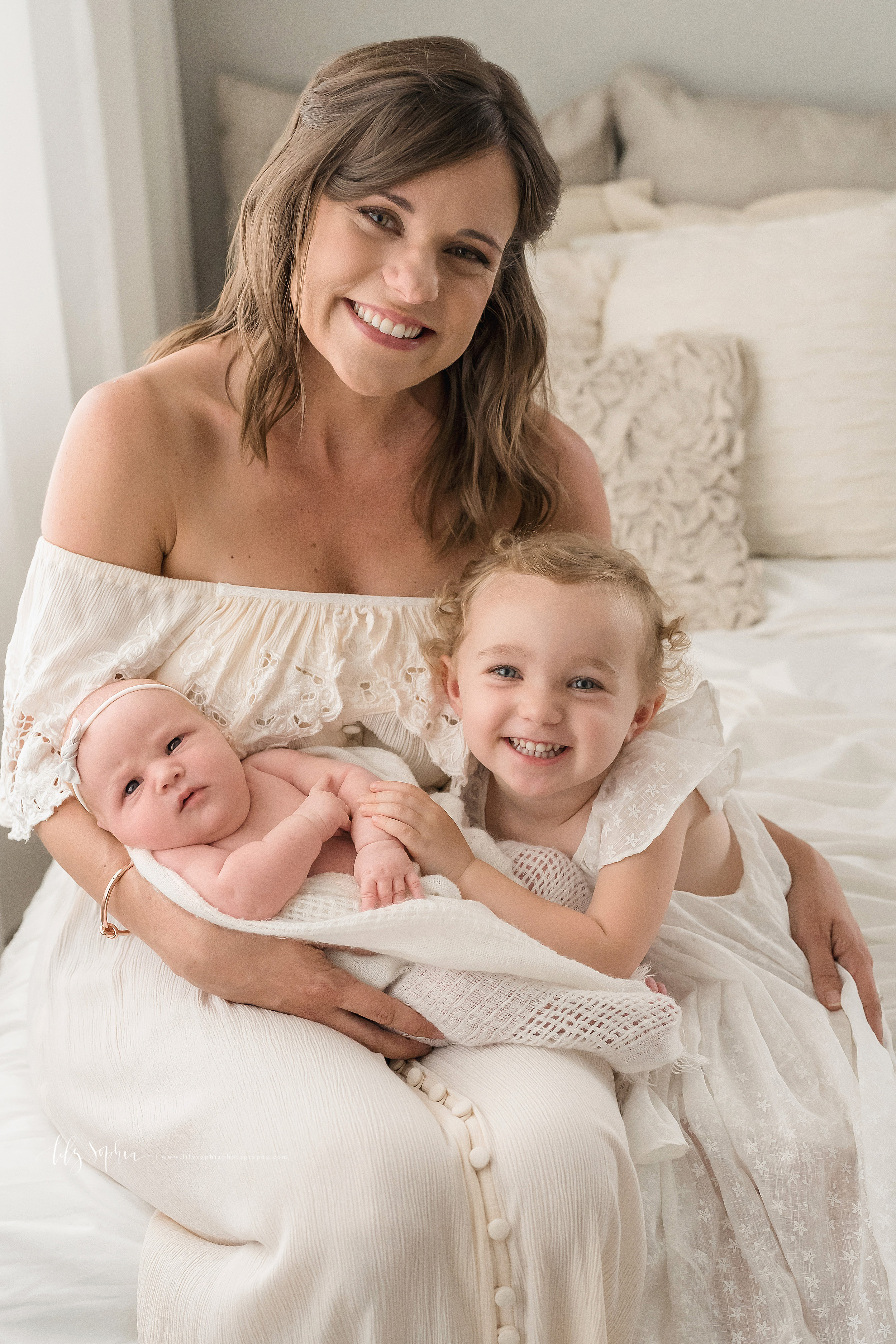 Family photo of an awake newborn, her smiling curly haired toddler sister and her proud and happy mom as mom sits on a bed and holds her newborn daughter on her lap and the toddler stands next to her taken in Atlanta, Georgia.
