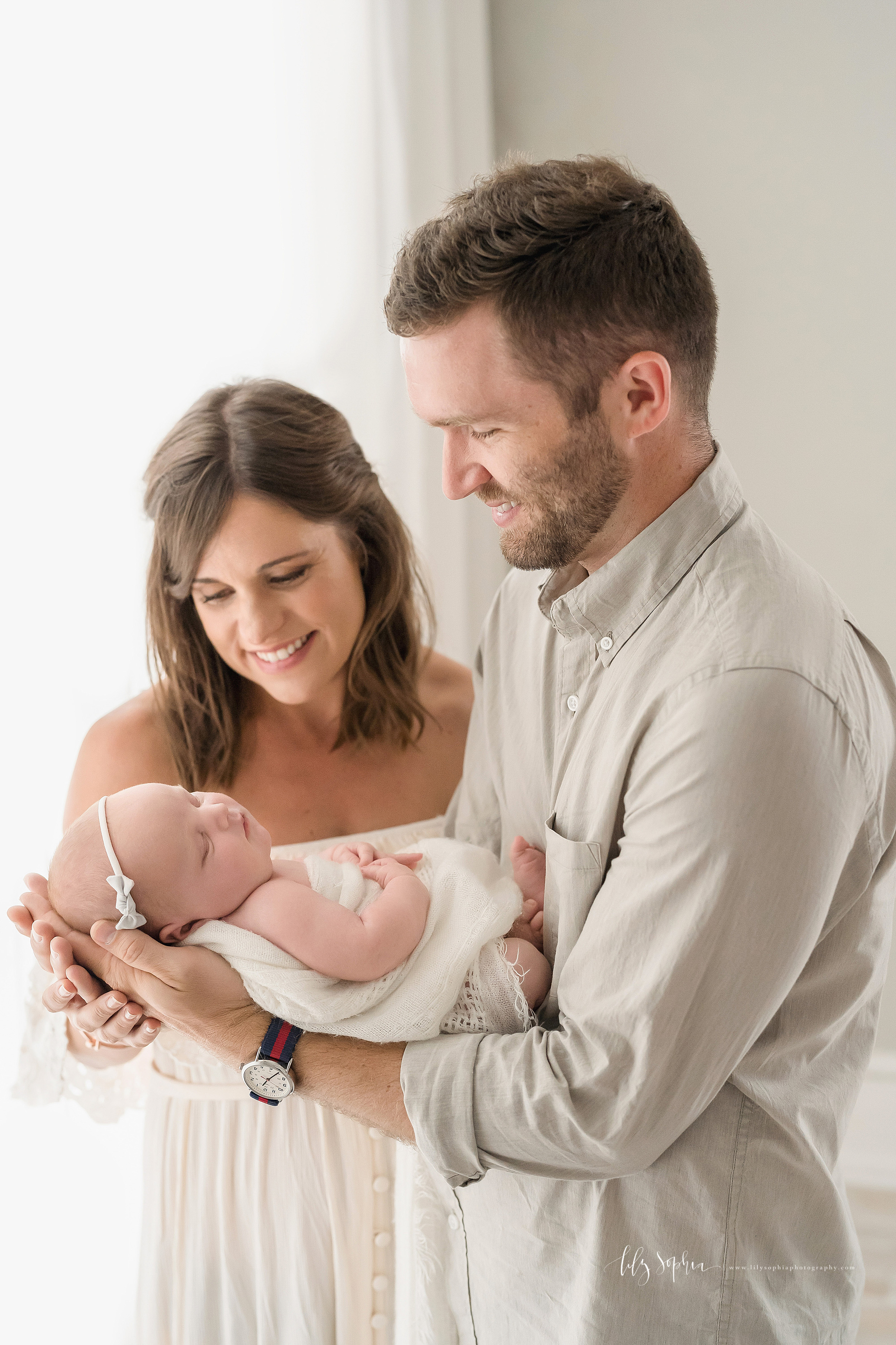 Family photo of three as dad holds his sleeping newborn daughter in his hands and mom tenderly looks on taken in a natural light Atlanta studio.