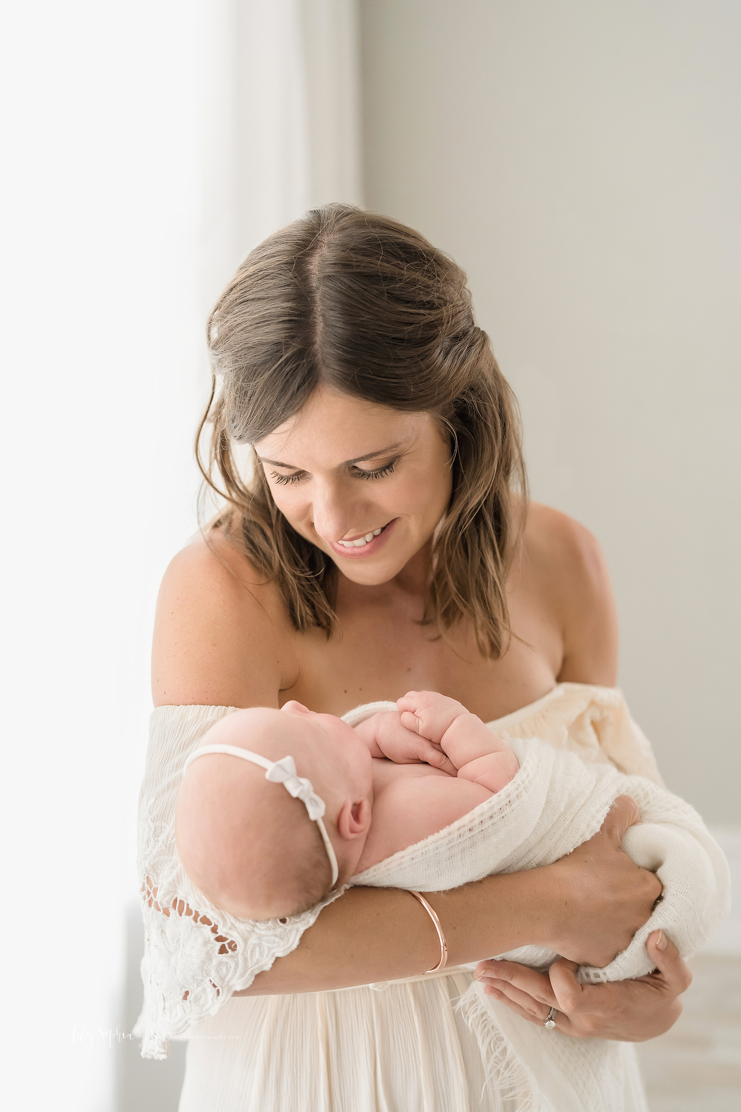 Newborn photo of a smiling and proud mother who is wearing an off the shoulder cream button downed gown holding her newborn daughter in her arms and proudly admiring her as she stands in natural light in an Atlanta studio.
