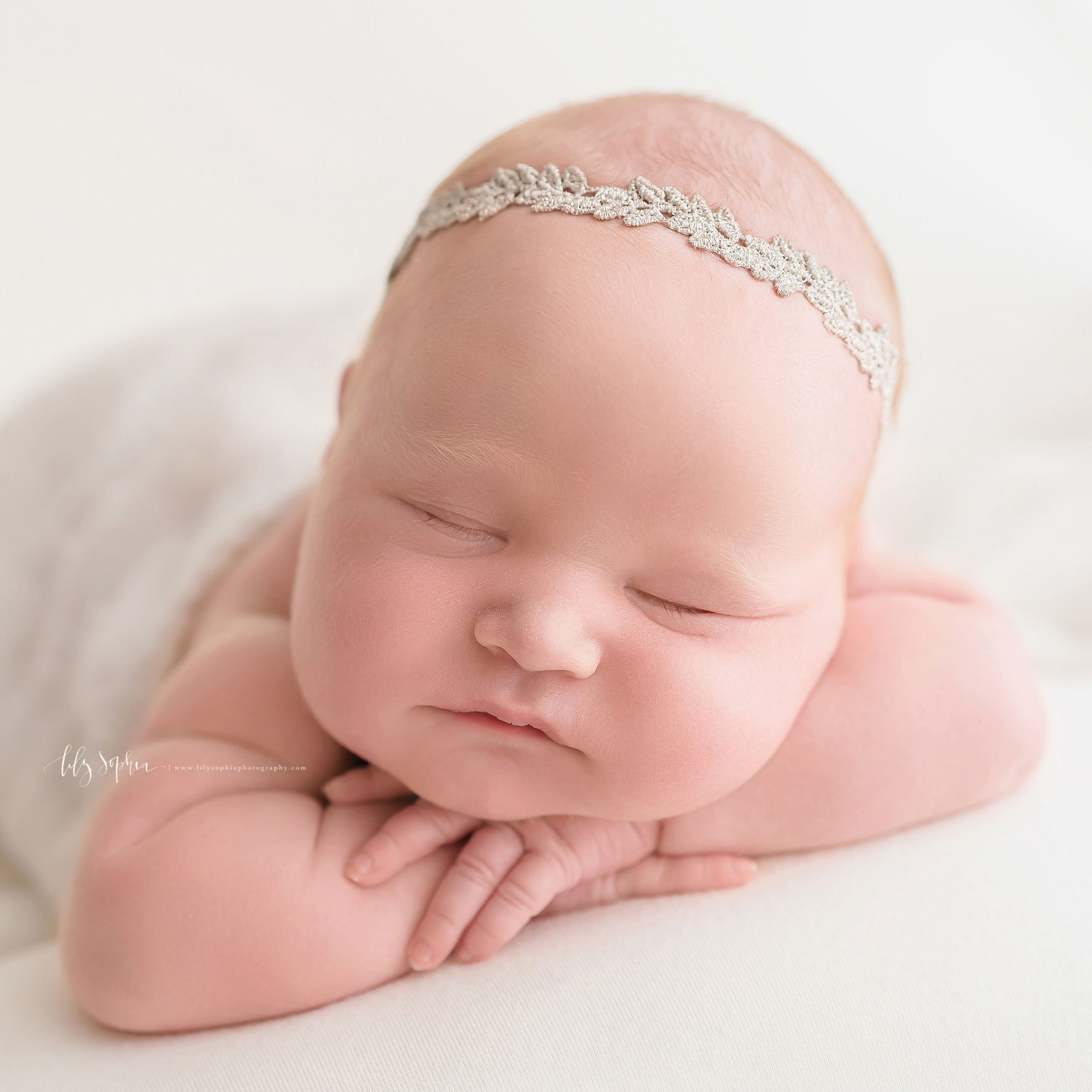 Newborn photo of a chunky baby girl as she sleeps with her hands crossed under her chin and wears a delicate headband in her hair in an Atlanta studio.