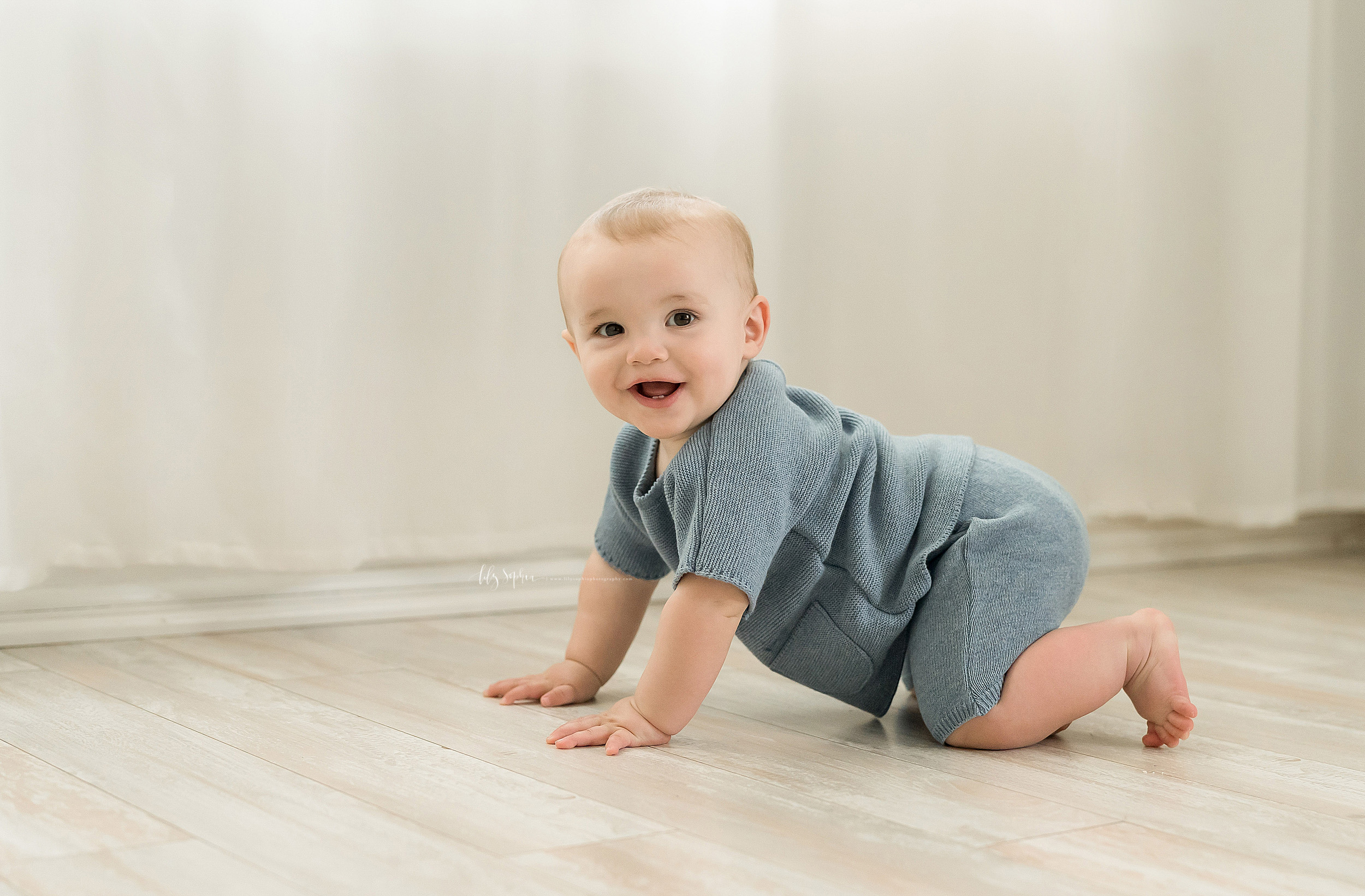 Milestone photo of an eight month old little boy crawling across the floor of an Atlanta studio in natural light.
