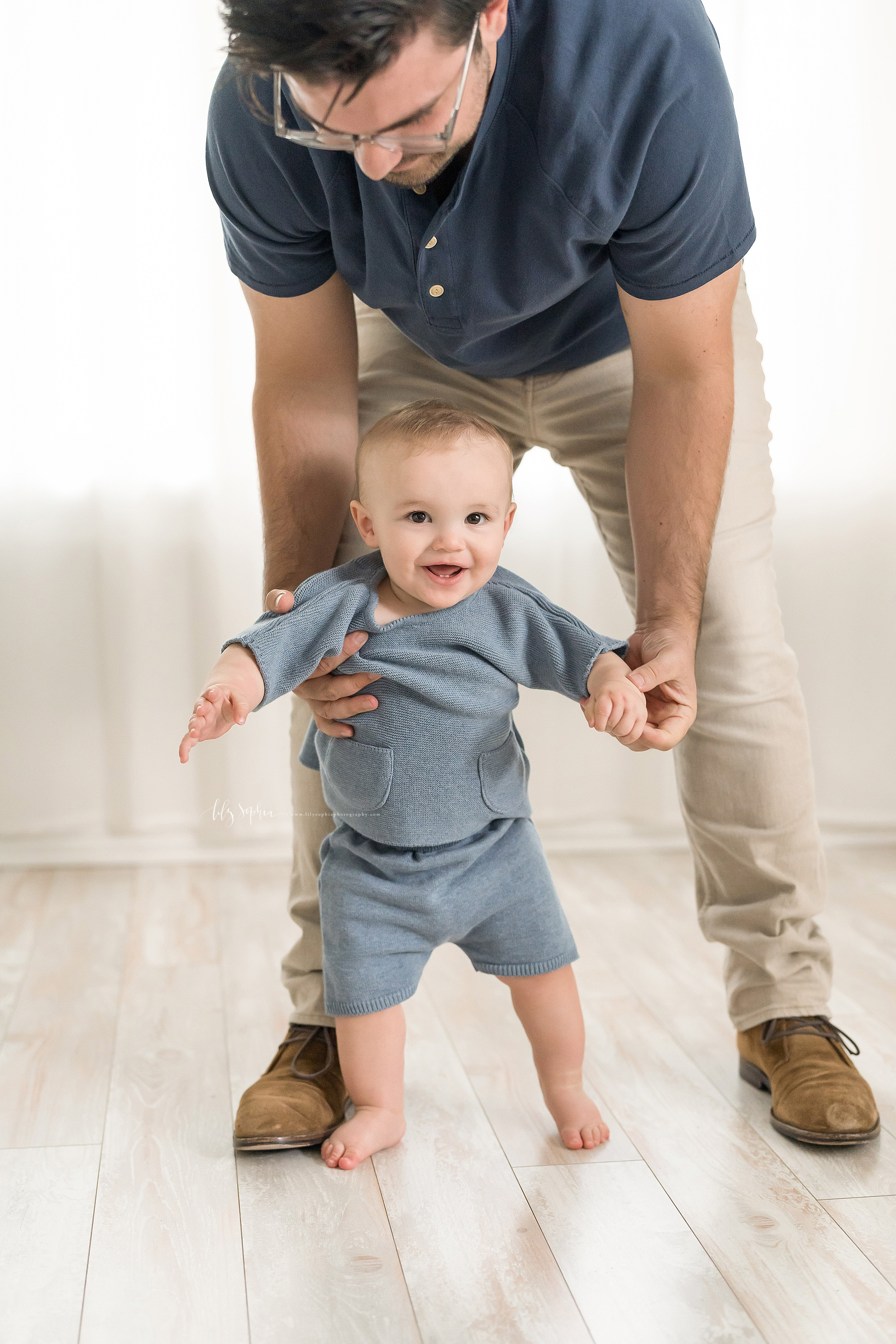 Photo of a dad and his father at the eight month old milestone with dad holding his son's hand and steadying him with his other hand as the son takes his first steps in a natural light Atlanta studio.