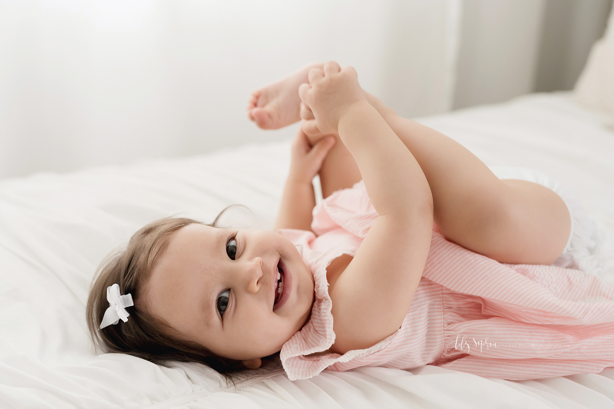 Milestone photo of a smiling nine month old baby girl as she lies on her back on a bed in a natural light Atlanta studio and plays with her toes.