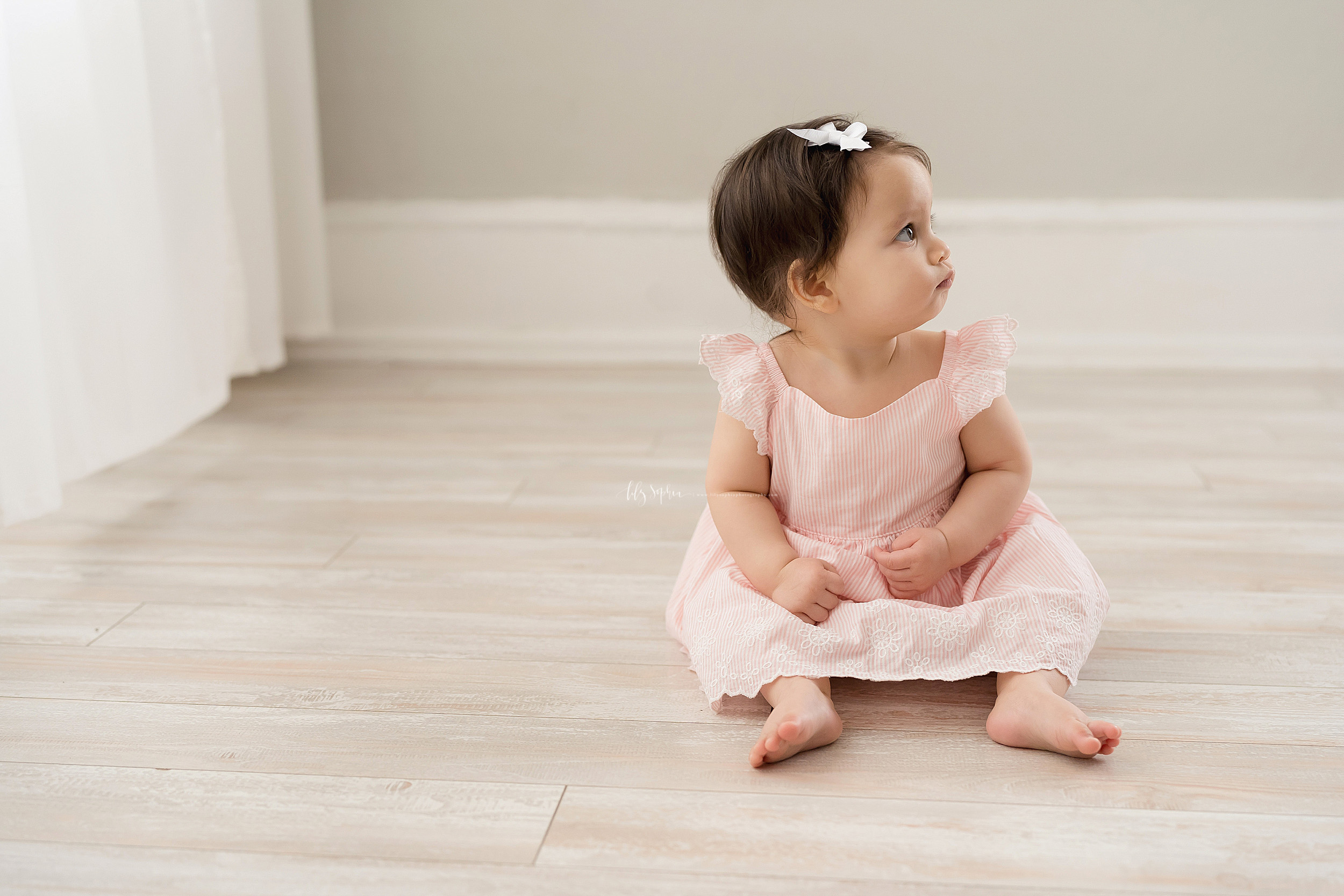 Milestone photo of a serious nine month old as she sits in natural light on the floor of an Atlanta studio.