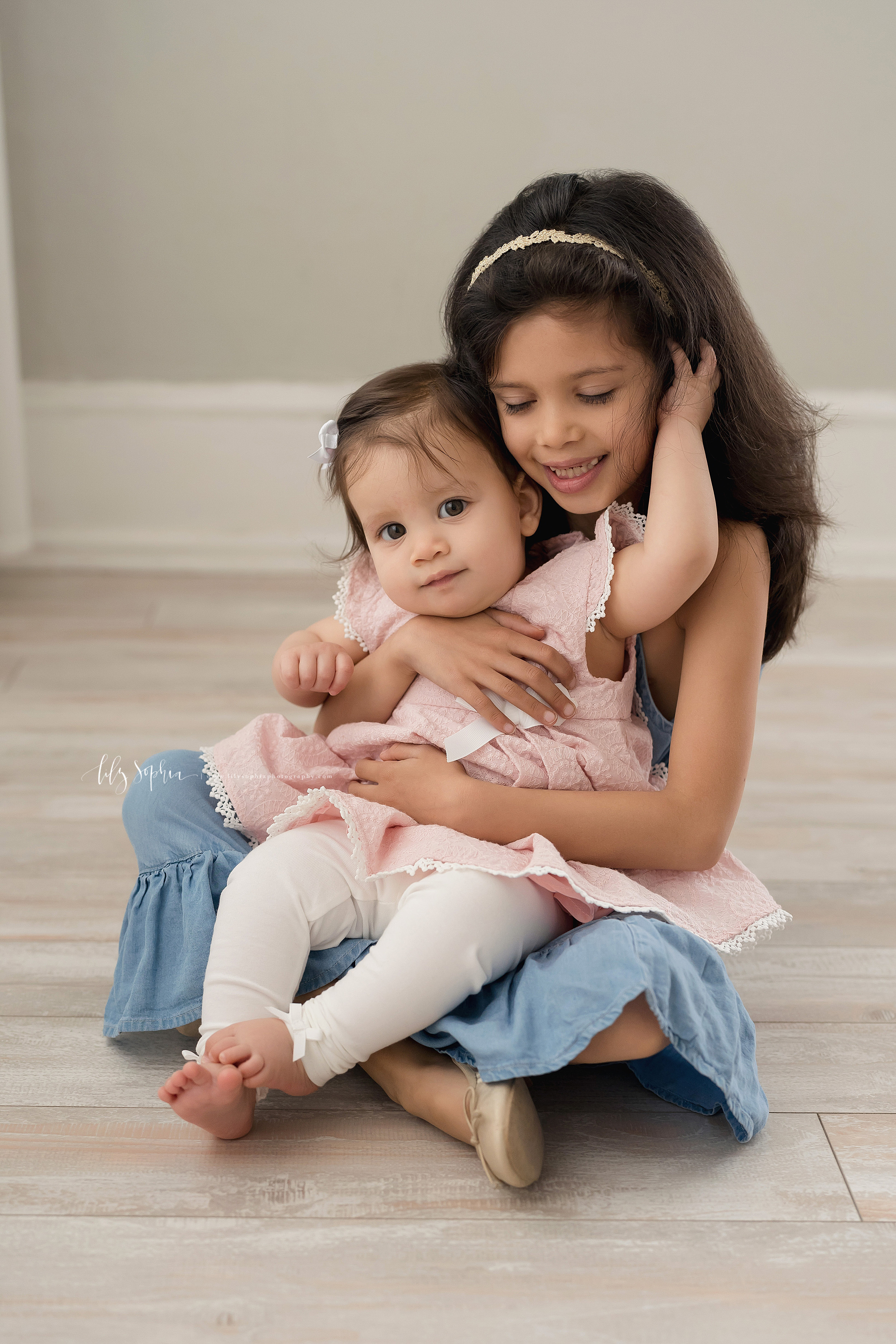 Sibling photo of two sisters as the older sister sits with her nine month old baby sister on her lap adoring her as her baby sister plays in her hair and they sit on the floor of an Atlanta studio in natural light.