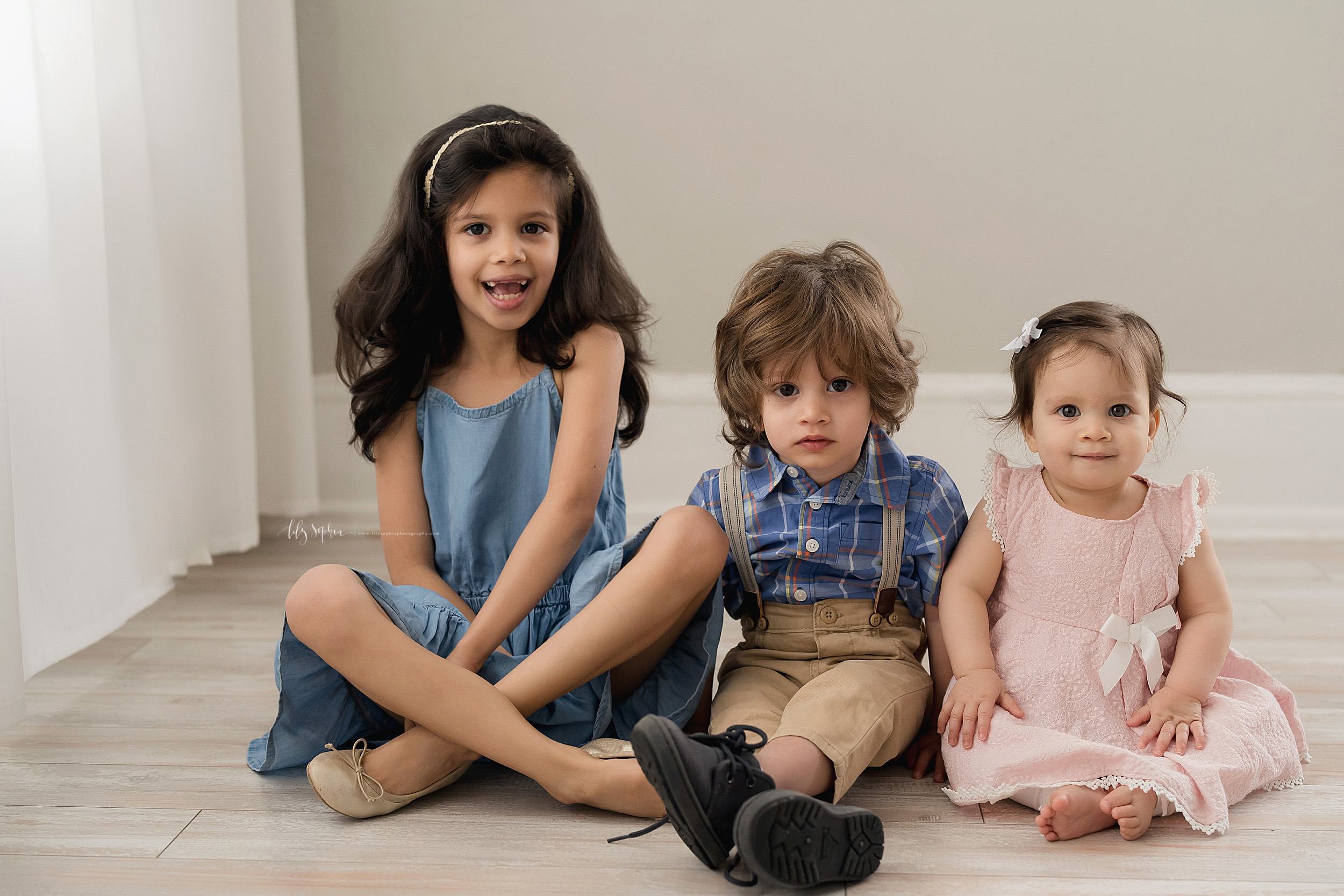 Family photo of a brother sitting between his two sisters on the floor of a natural light Atlanta studio.