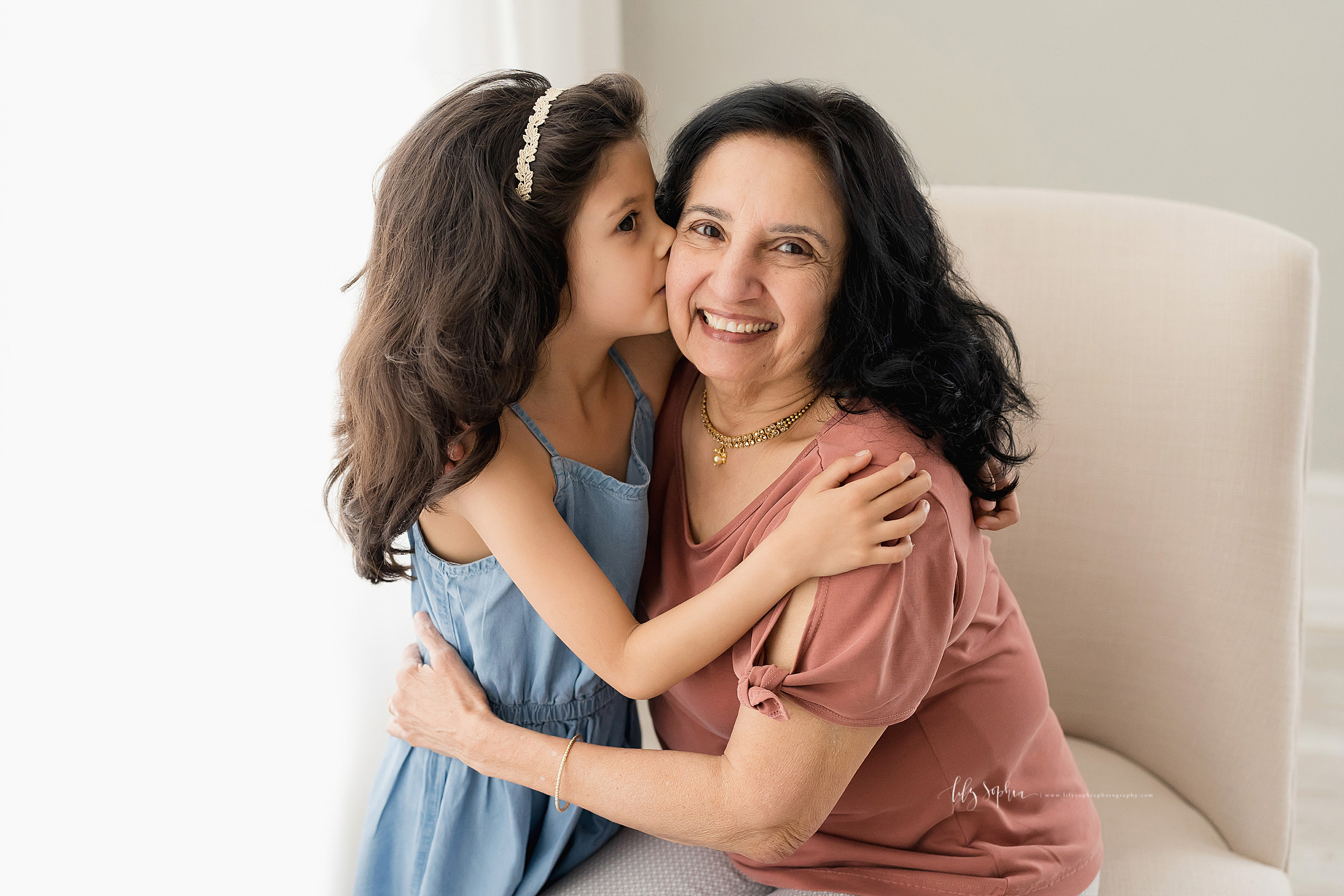 Family photo of a granddaughter standing next to her grandmother in a natural light studio as the two embrace and the granddaughter kisses her grandmother on the cheek in Atlanta, Georgia.