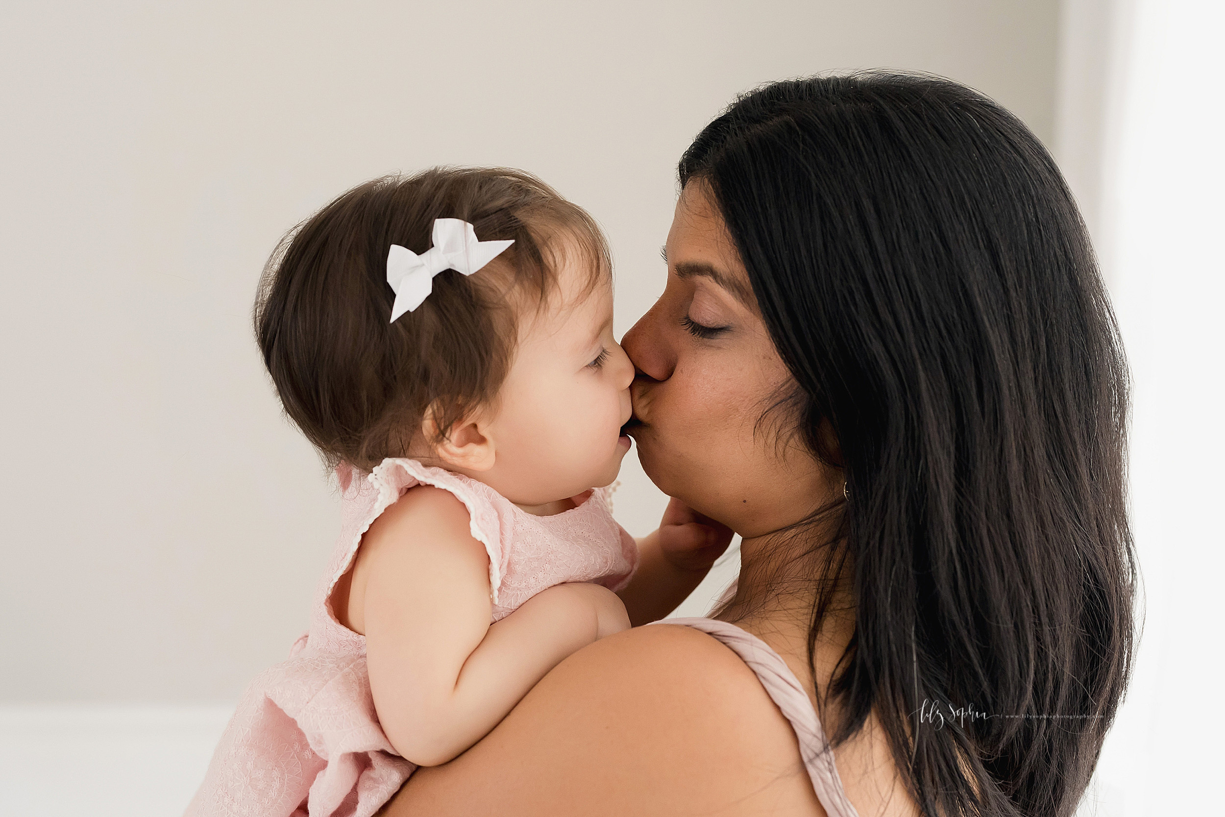 Milestone photo of a mom holding her nine month old daughter in a studio in Atlanta as they kiss one another in natural light.