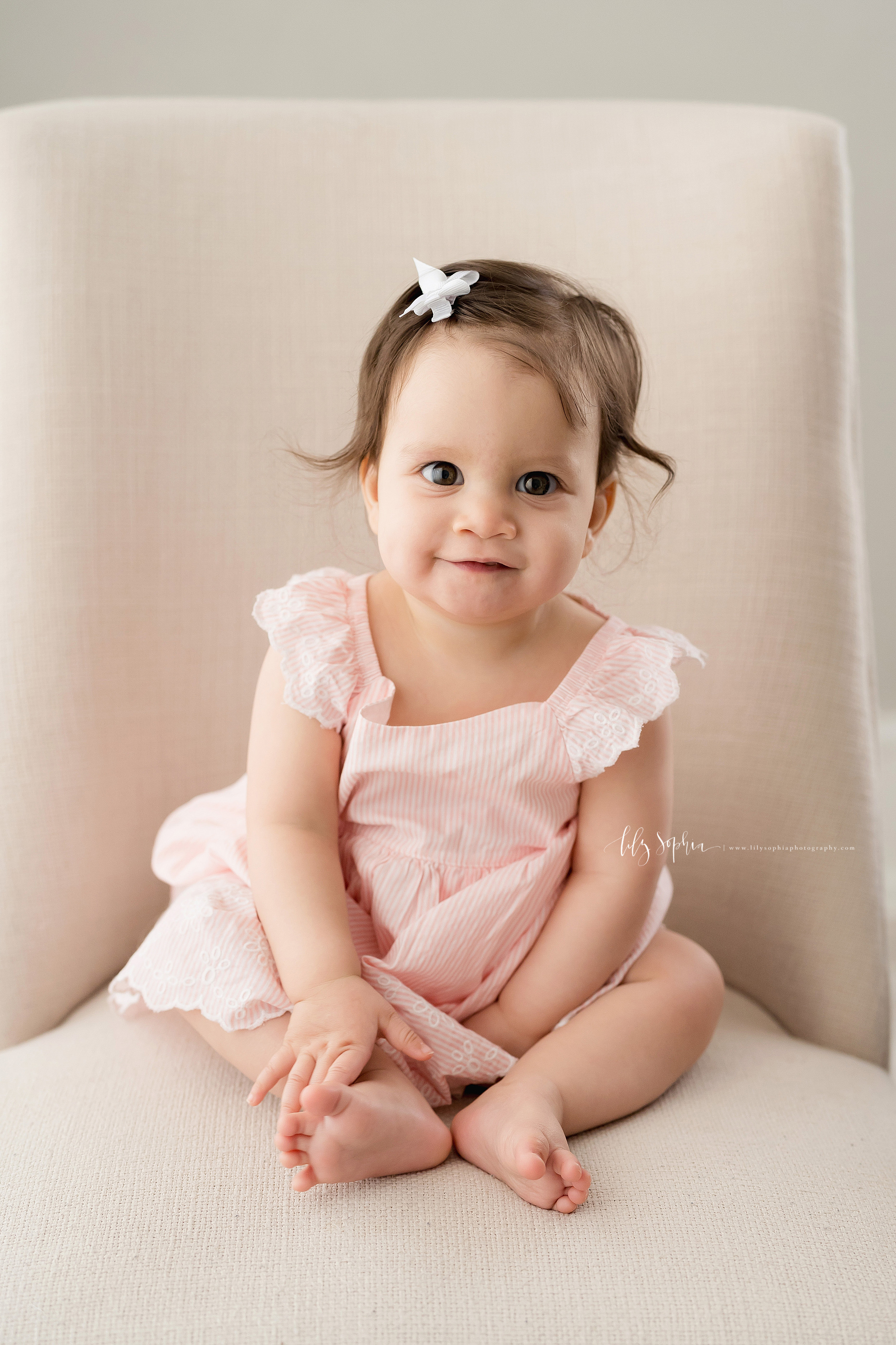 Milestone photo of a nine month old baby girl as she sits in a tan armless chair in natural light in an Atlanta studio.