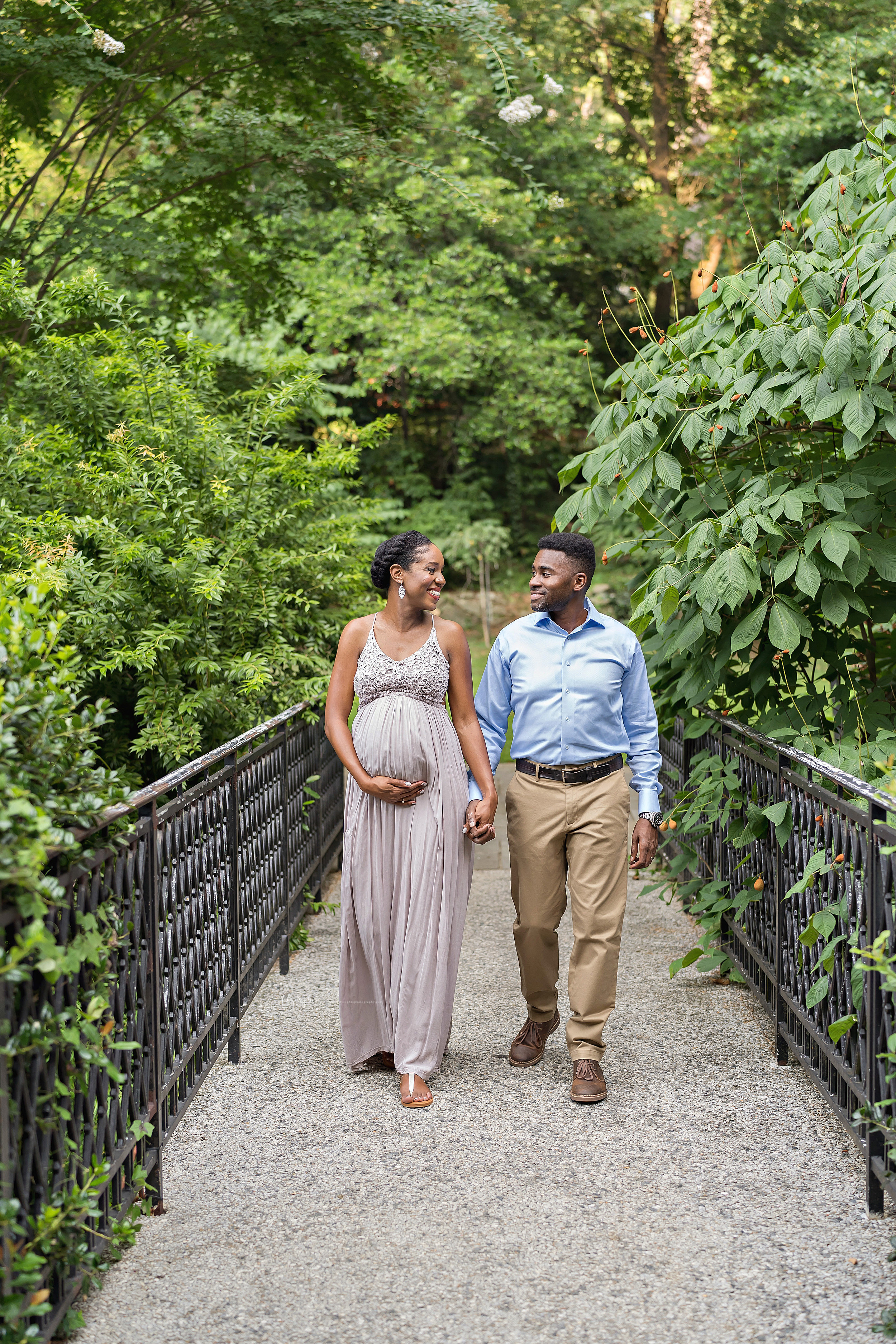Maternity photo of an African-American husband and wife as they walk hand in hand over a wrought iron bridge at sunset in an Atlanta garden.