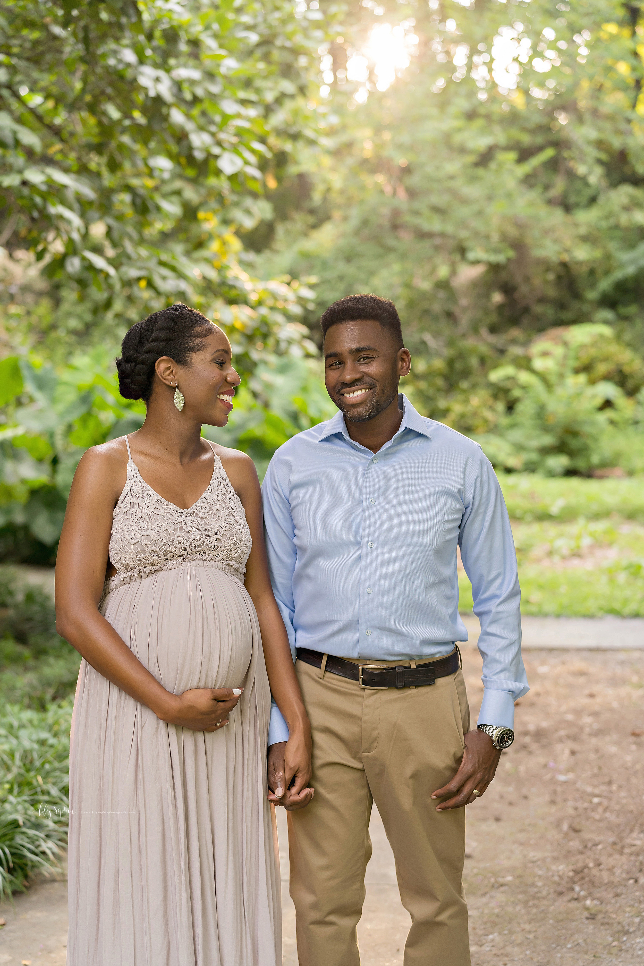 Maternity photo of a happy African-American couple as they stand hand in hand in an Atlanta garden at sunset.