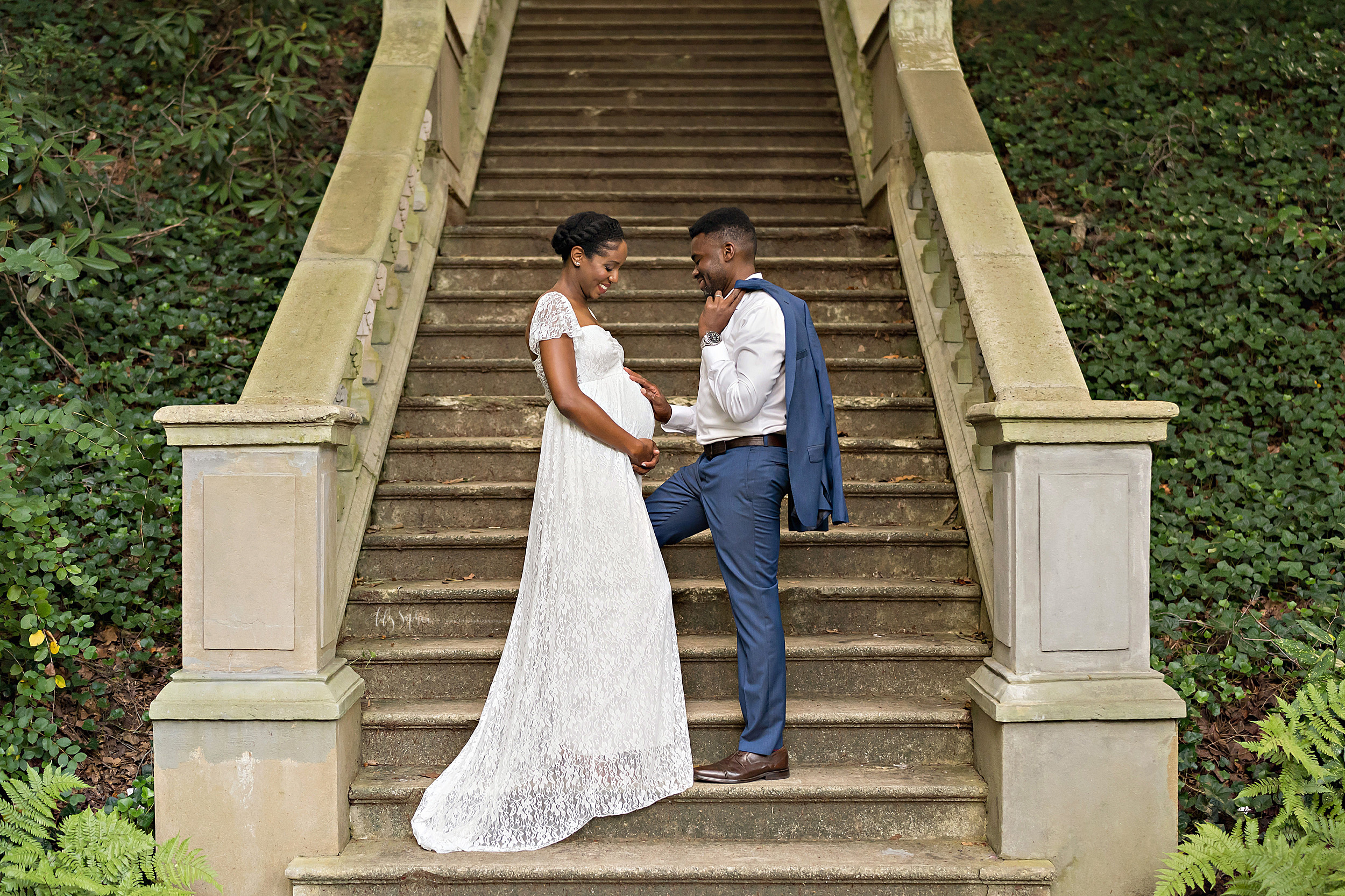 Maternity photo of an African-American husband and wife as they stand at the base of a stone staircase in an Atlanta garden at sunset with the father holding his blue suit jacket over his shoulder and touching his newborn in utero and his wife clasping her hands below her belly as she wears a lace bell sleeve full-length gown.
