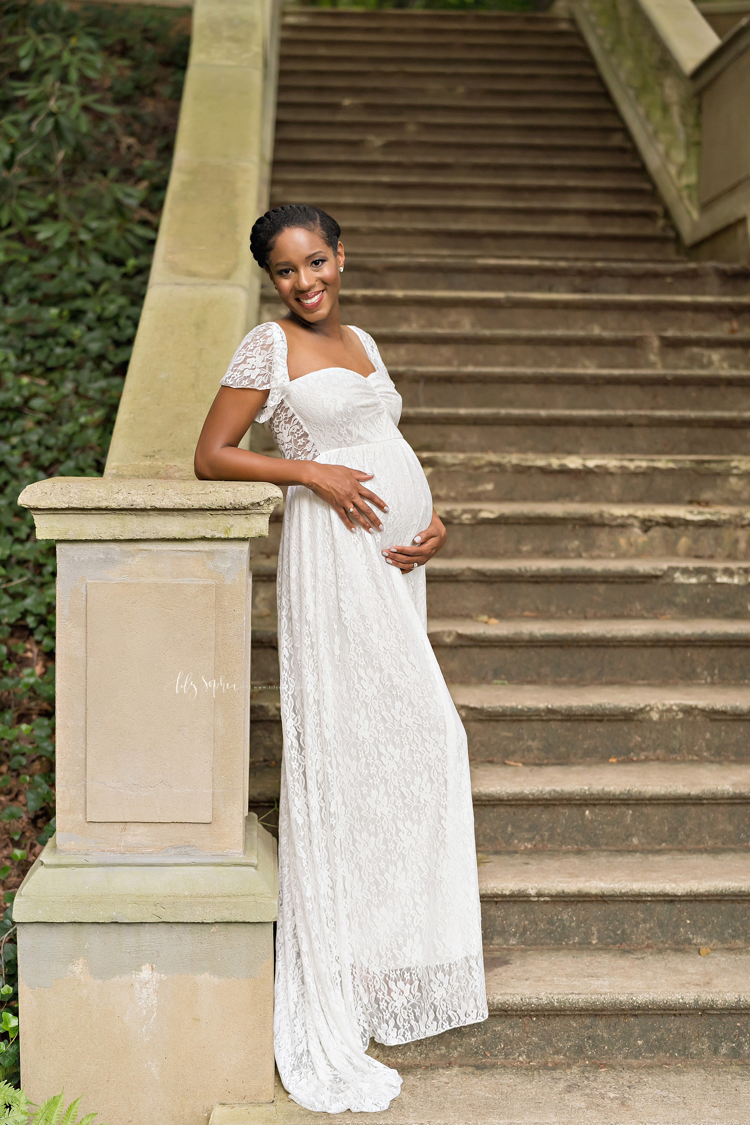 Maternity photo of an African-American woman wearing a lace overlay full-length gown with short bell sleeves as she stands at sunset at the base of a stone staircase and leans with her right elbow on the newel post of the stone bannister in an Atlanta garden
