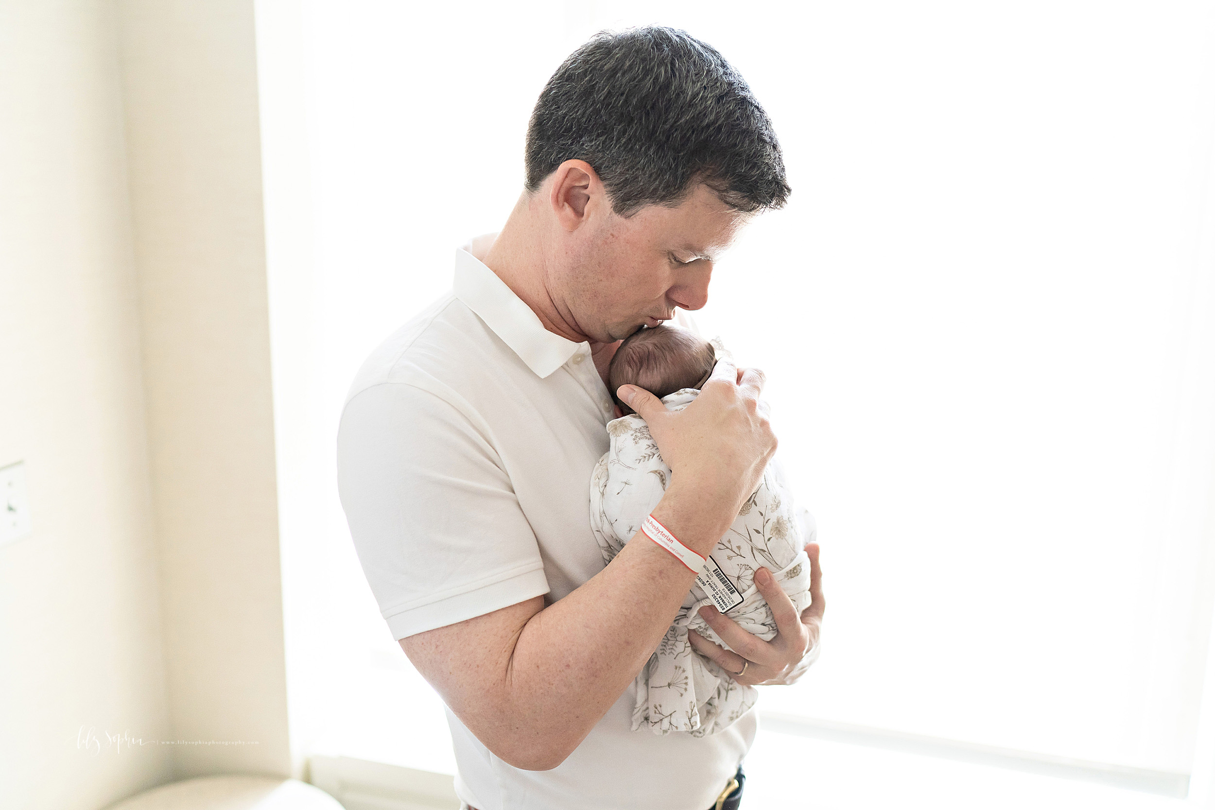 Photo of a dad carefully embracing his newborn daughter as he stands with her in natural light in the hospital room in Lenox Hill, New York shortly after her birth.