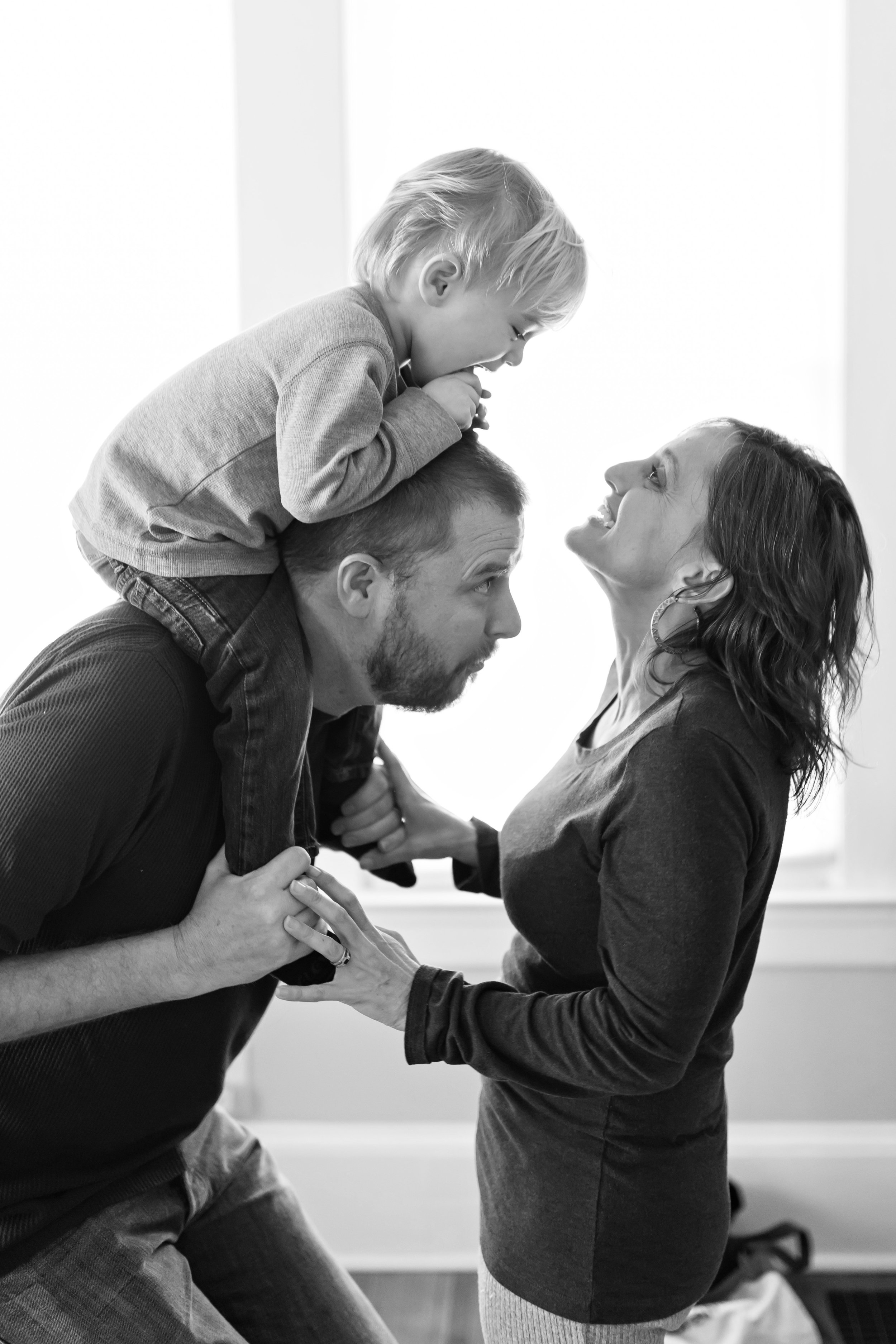 Black and white in-home photo of a family of three as dad holds his son on his shoulders and mom reaches up to see him while they play peek-a-boo in their Atlanta home.