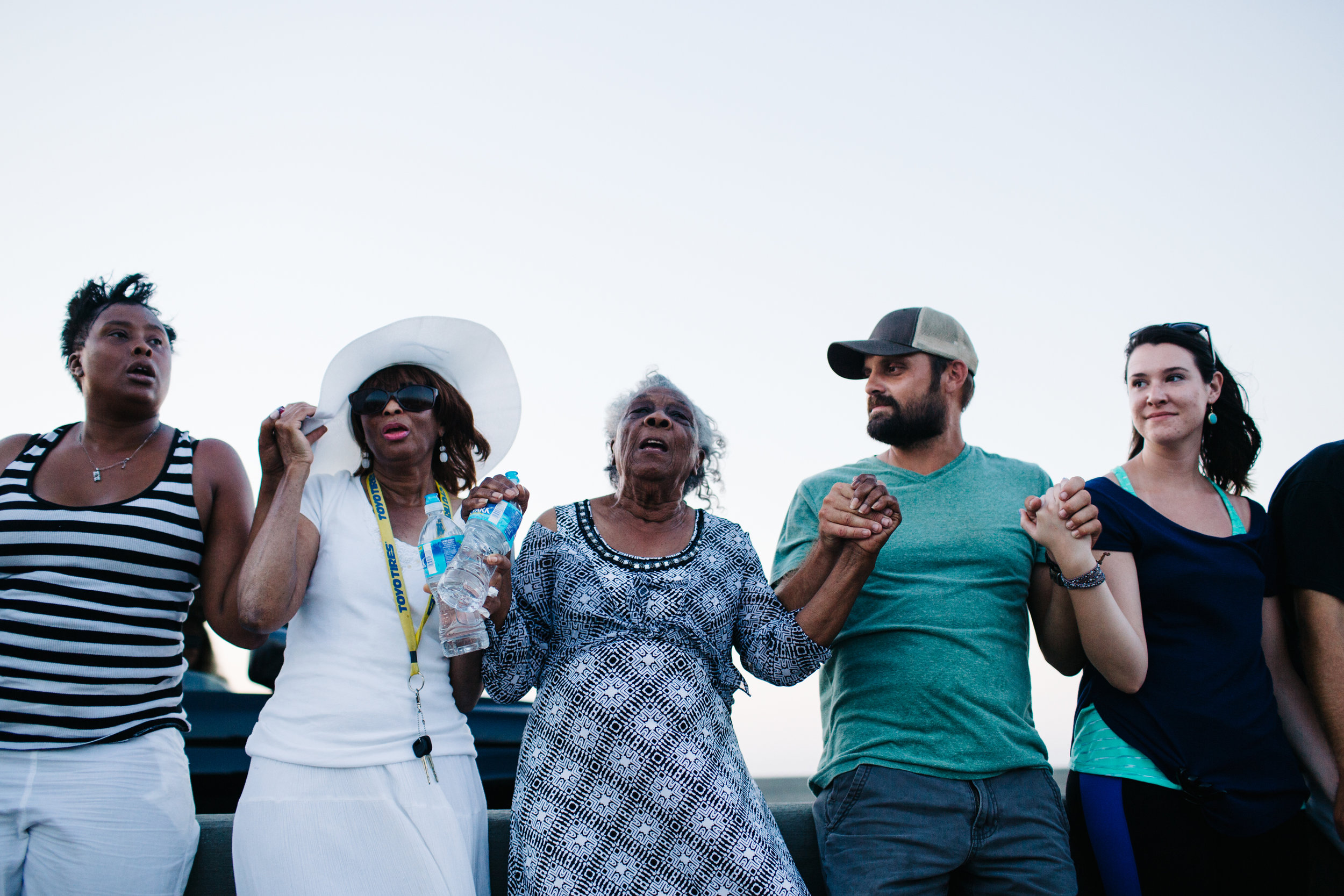 Supporters sing and join hands at the top of the Arthur Ravenel Jr. Bridge to celebrate and honor the lives of the nine victims of the Emanuel A.M.E. Church shooting.