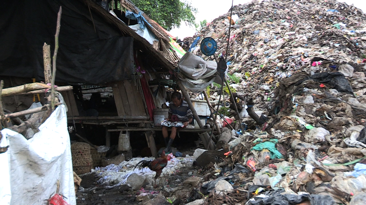 Families live beside rotting, stinking garbage that often threatens to engulf them