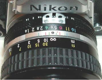 The lens is focused at infinity and in visible light (black dot aligned with the∞symbol).