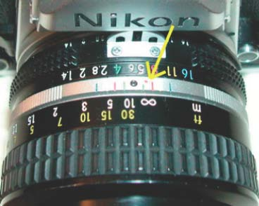 The lens is focused at infinity for IR photography (tiny red dot aligned with the∞symbol, as shown by the yellow arrow).