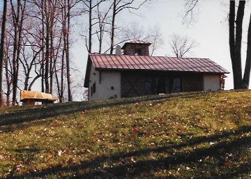 "Bench in Flight I,  1994, 3'6"" x 6' x 2'6"", white oak. Shown outside my rural Virginia hut."