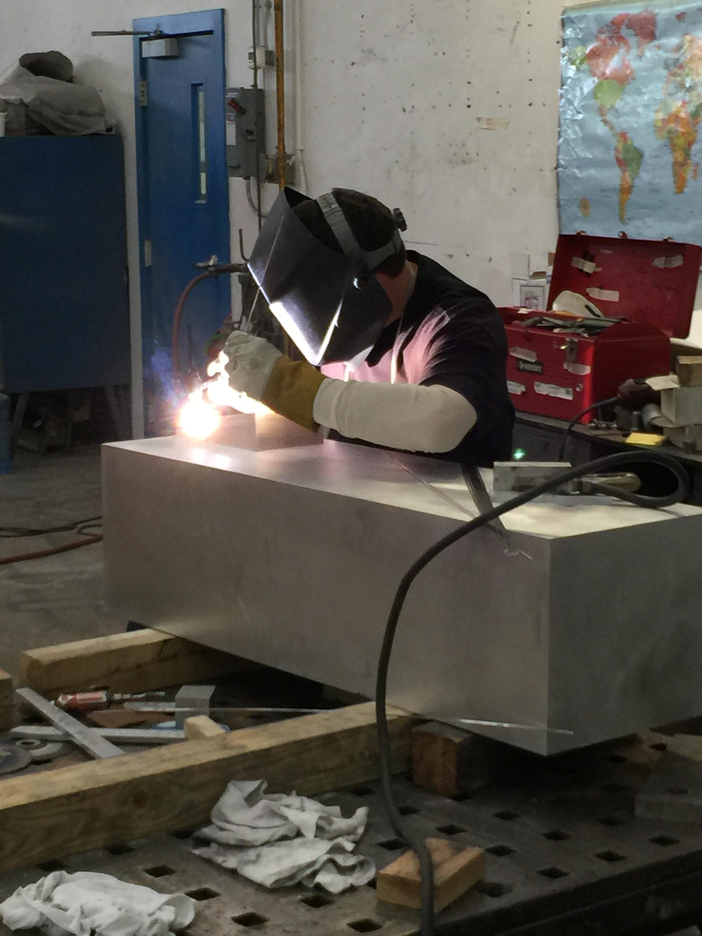 A welder works on a sculpture by Joel Shapiro.