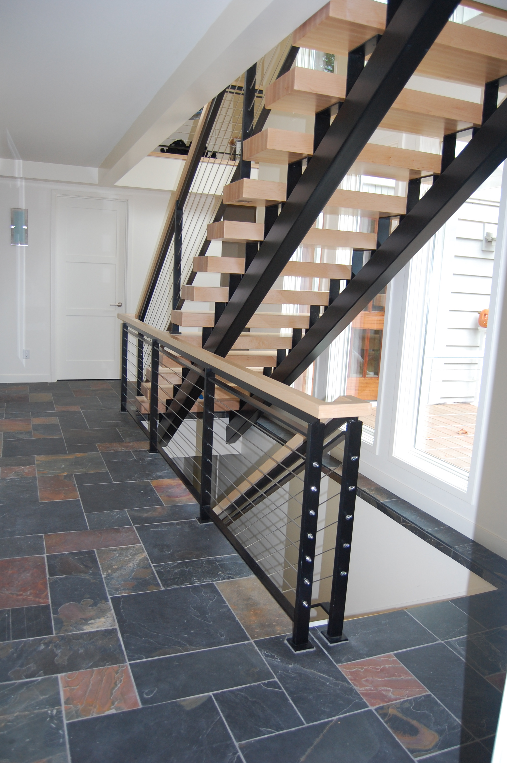 Staircase built out of steel with flat bar cable railing.  Designed by MCM Construction