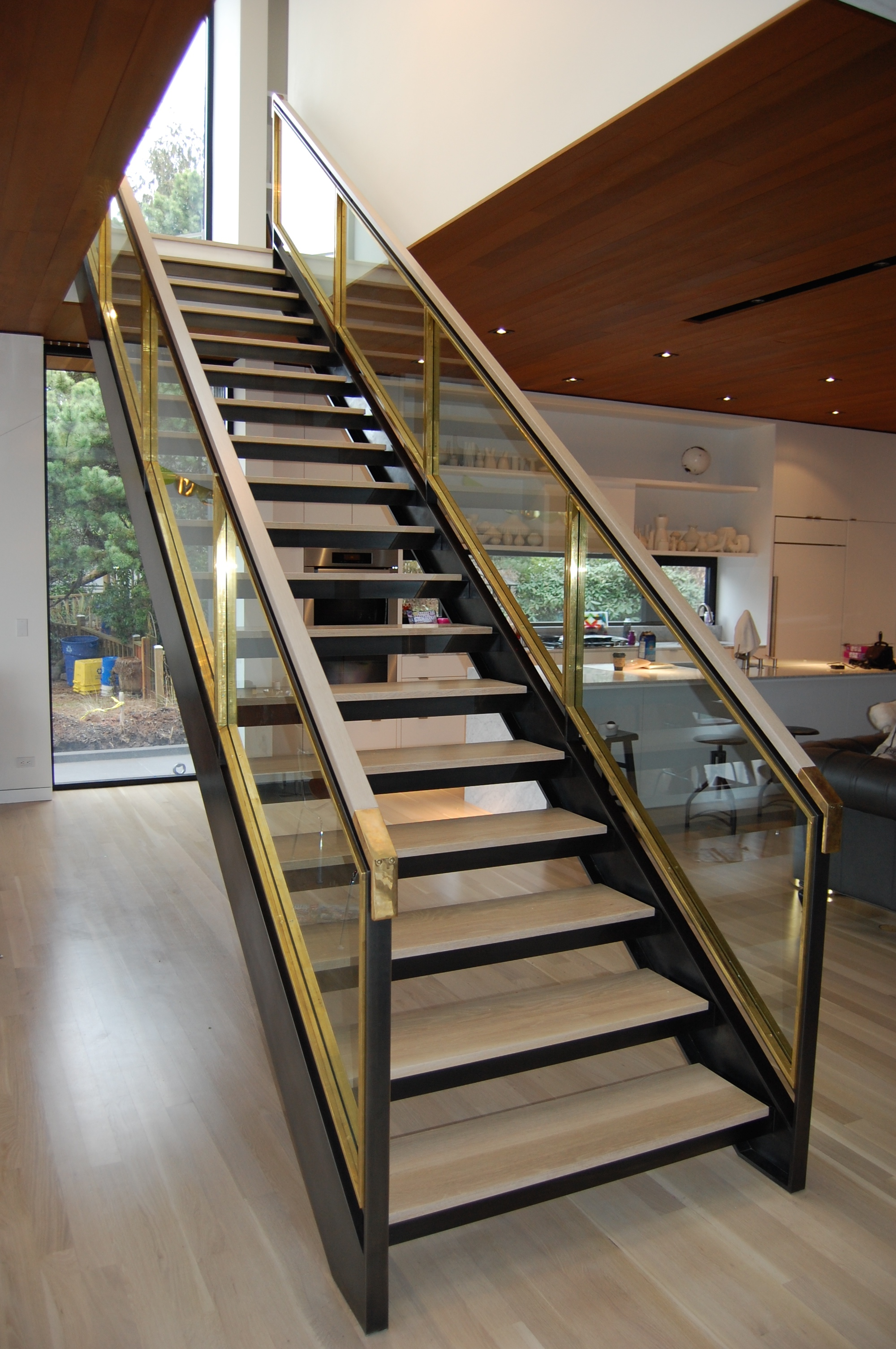 Staircase built out of blackened steel, brass and glass. Glass is stopped in on both sides with solid brass flat bar. Sides are fabricated channel with fully welded seams that were ground and sanded.  Solid brass handrail ends transition into oak grab rails.  Designed by Paul McKean Architects
