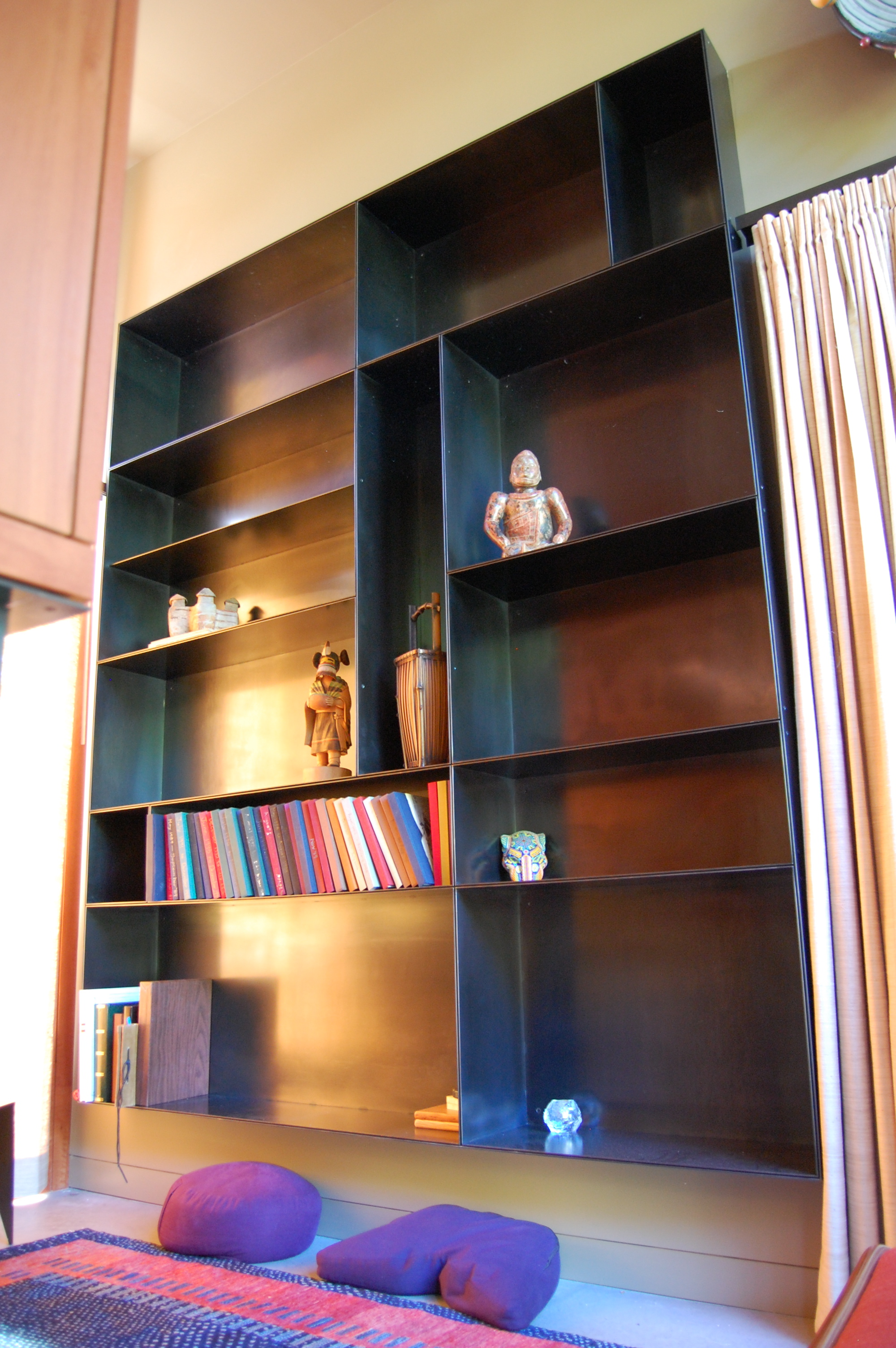 Built in book shelves. Each shelf is an individual hot rolled steel box.  Designed by Eggleston/Farkas Architects