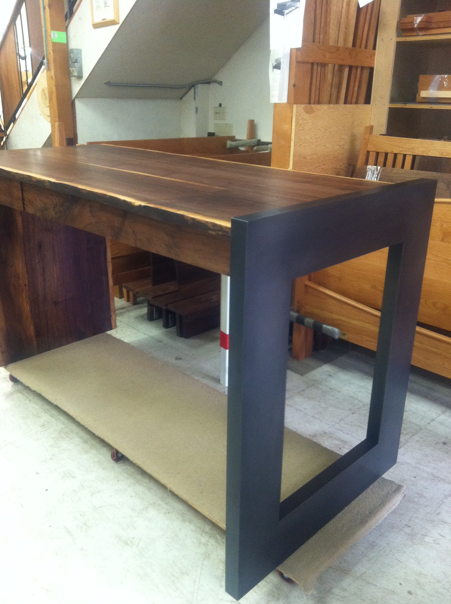 This blackened steel leg is attached to a live edge desk. Wood done by The Joinery.  Designed by The Joinery