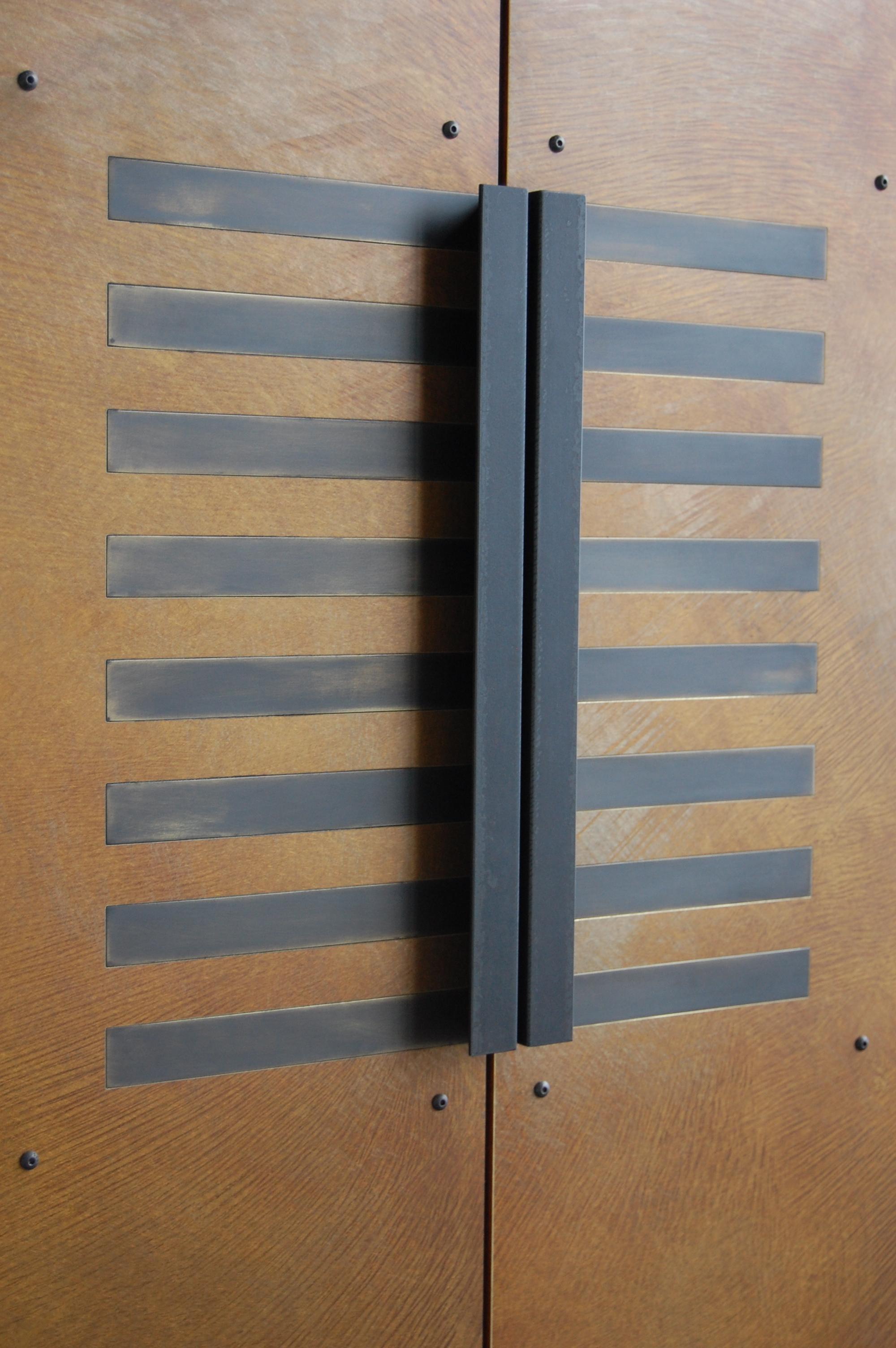 Cabinet doors with brass veneer with patina and blackened brass inlay. Custom steel handles.  Designed by Hensel Design Studios