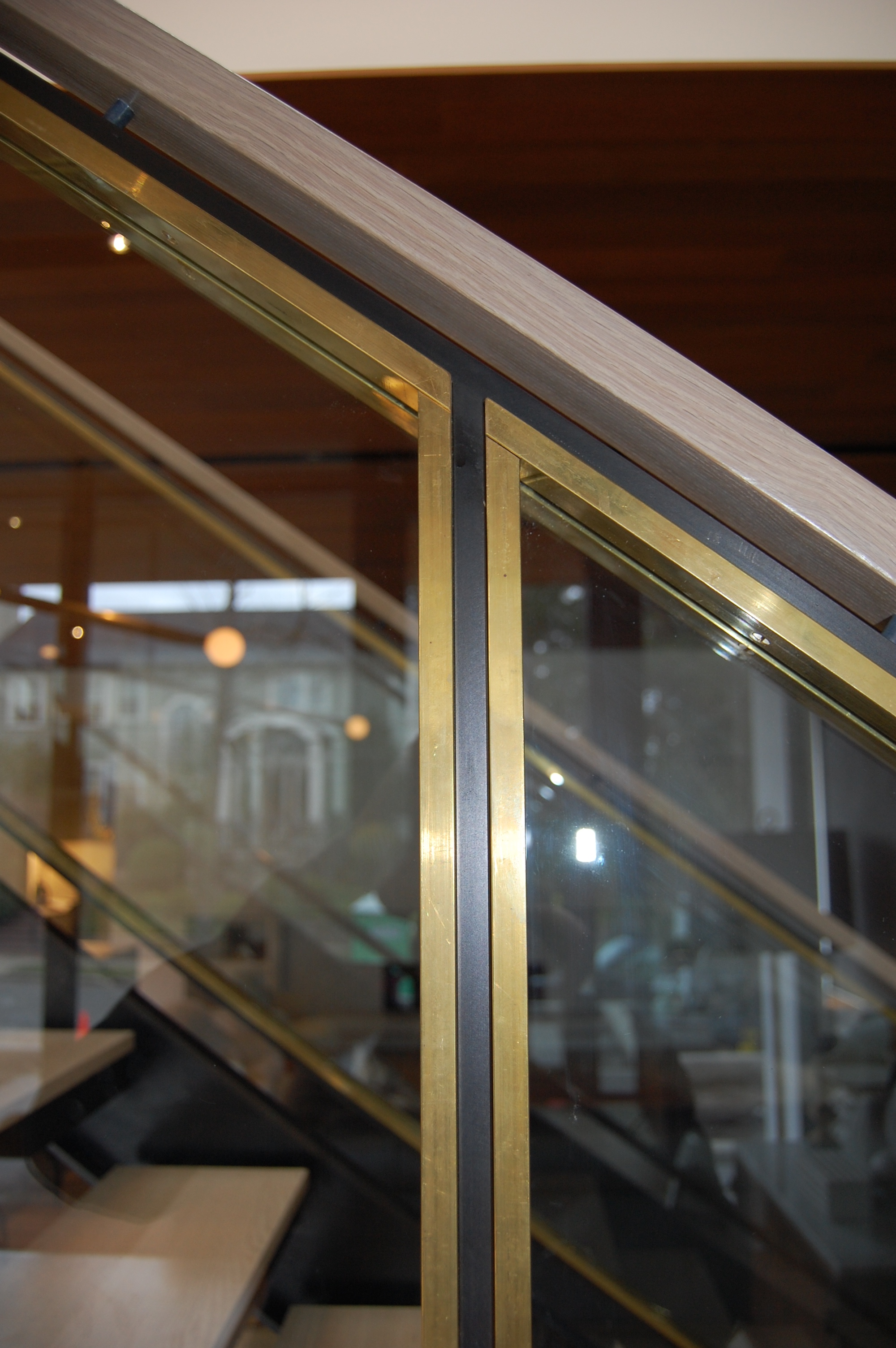 Blackened steel staircase and railing. Brass stops in and out to hold glass in place.  Designed by Paul McKean Architecture