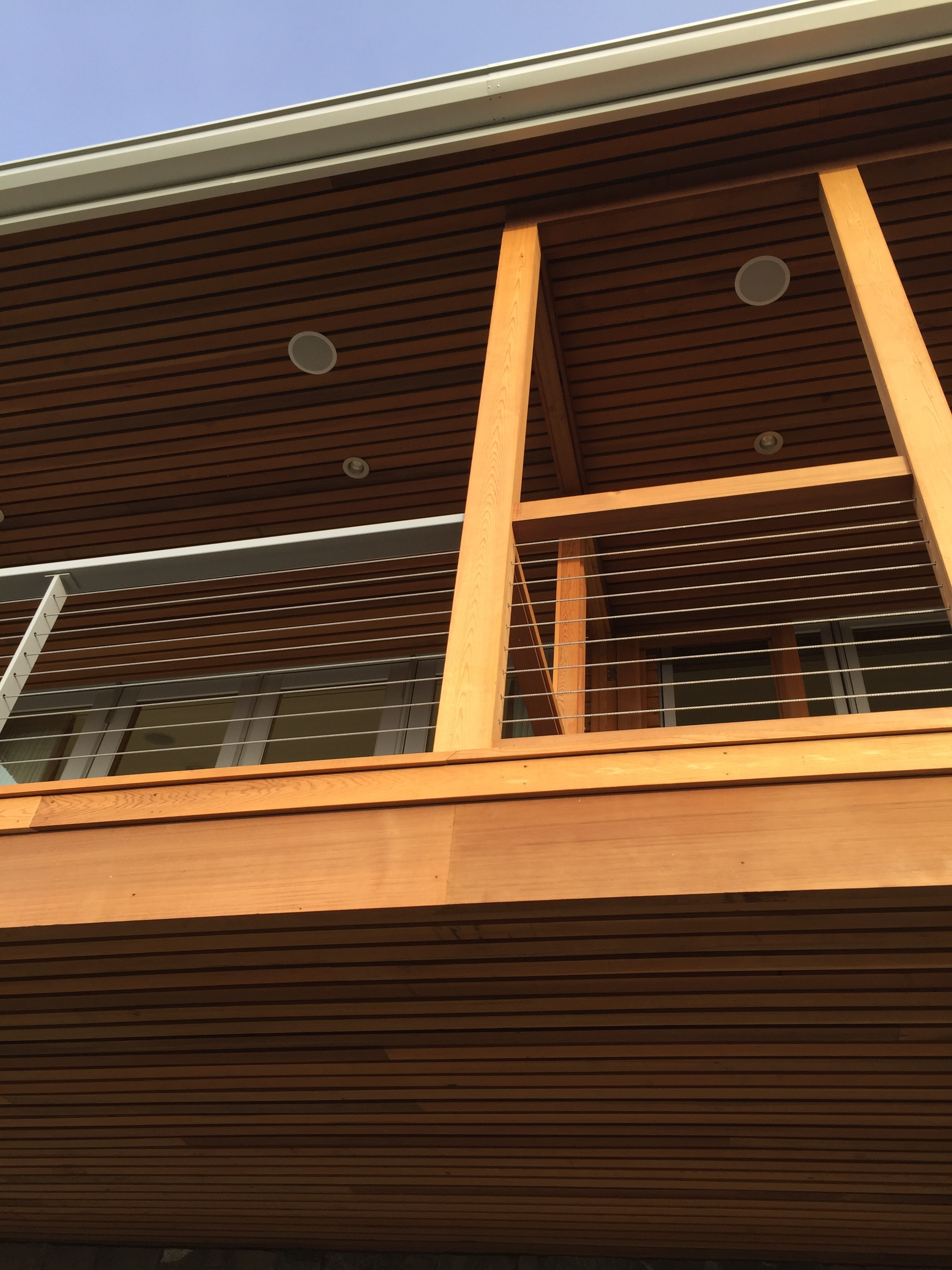 Steel railing that transitions into a wood screen porch. Cable carries through.  Designed by Pete Retondo Architecture