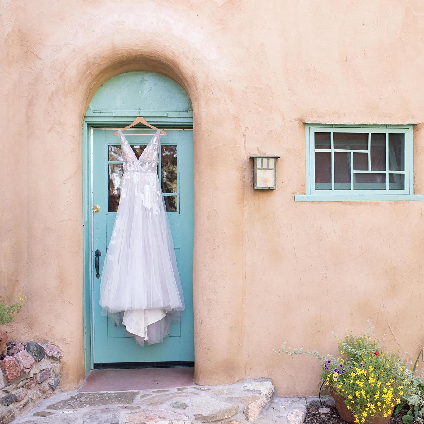 wedding dress hangs on turquoise door on adobe building in santa fe
