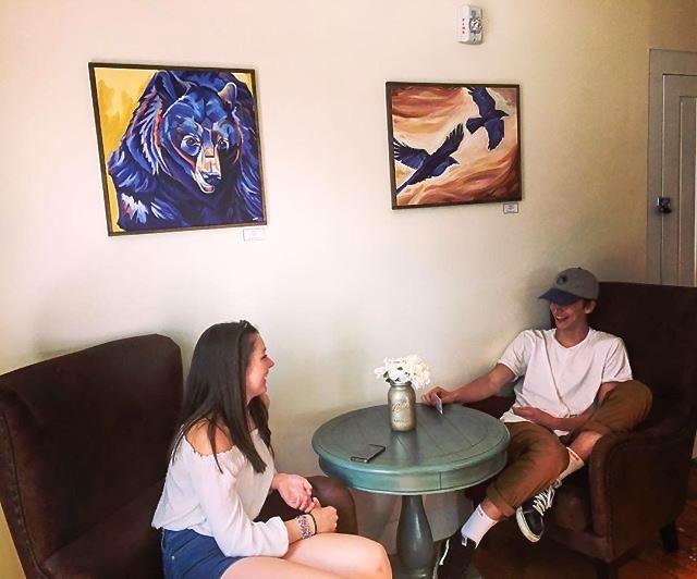 Mon Vert Cafe patrons chat beneath two original paintings, Woodstock, VT, 2017