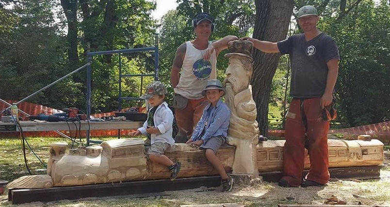 Artists Kevin Bendig and Doug Lindelbach pose in front of the History of the Railway tree that has incorporated the original rails which were donated by Canadian Pacific Rail to complete the piece.