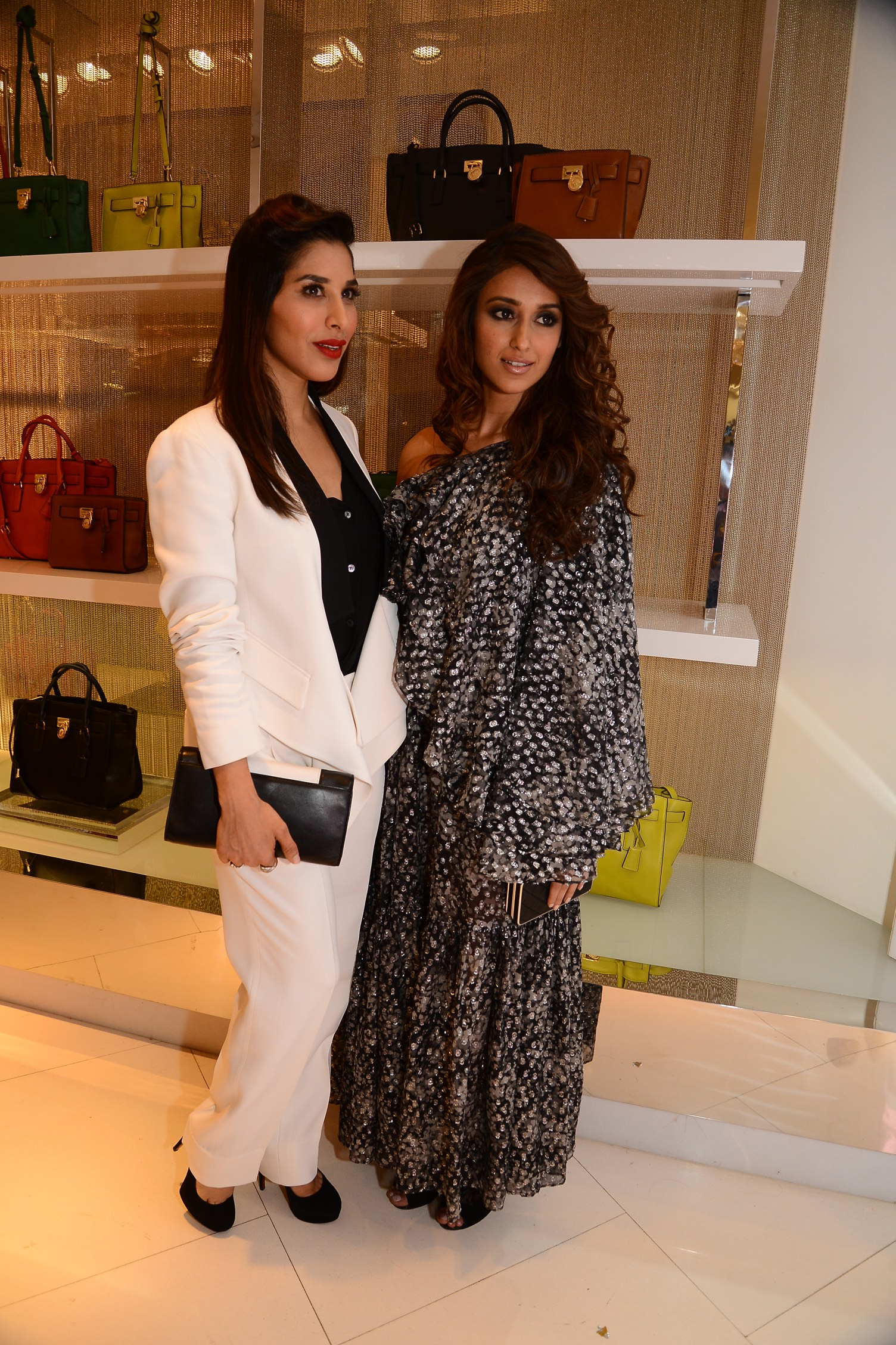 Sophie Choudry:    Optic white   Michael Kors jacket and pants with a black shirt all from the Transeason 2014 collection with a black and white leather Callie MICHAEL Michael Kors clutch from the Holiday 2015 collection.