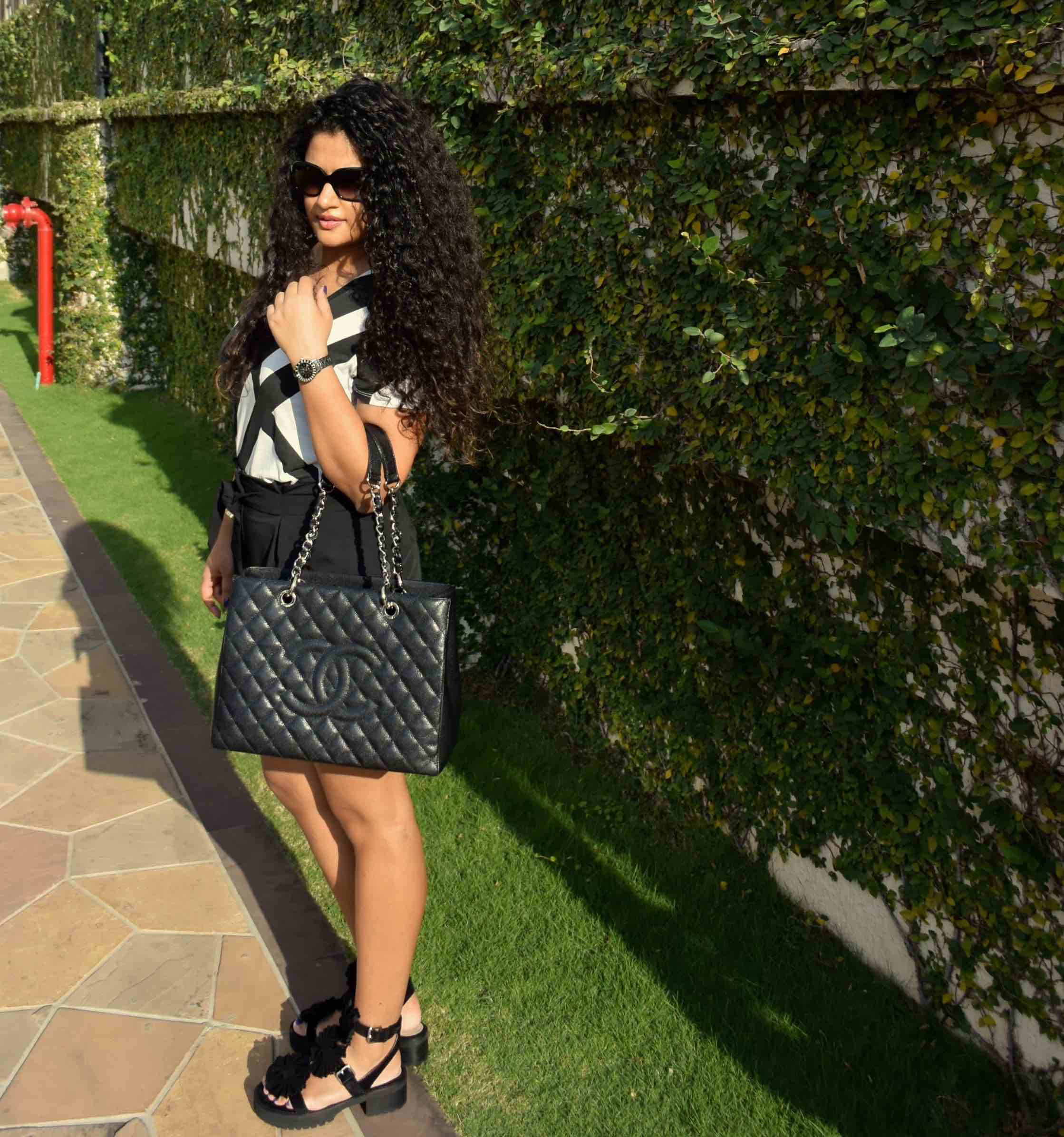 Shorts - Asos, T-shirt - Armani Exchange, Bag -Chanel, Sandals - Chloe for Opening Ceremony, Watch - Dior & Sunglasses - Chanel.