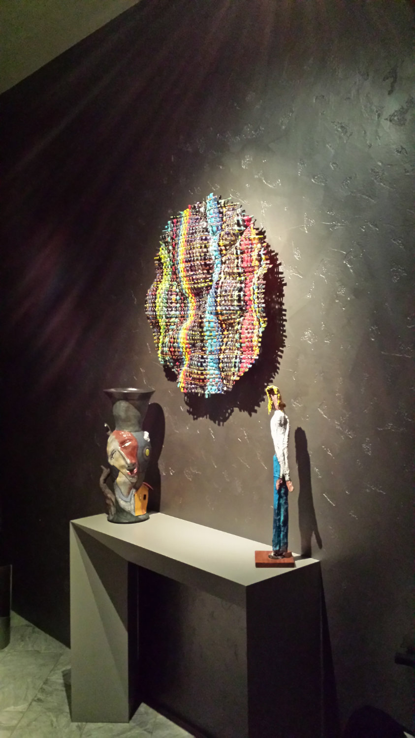 round-woven-glass-weaving-on-wall-over-art-sculptures.jpg