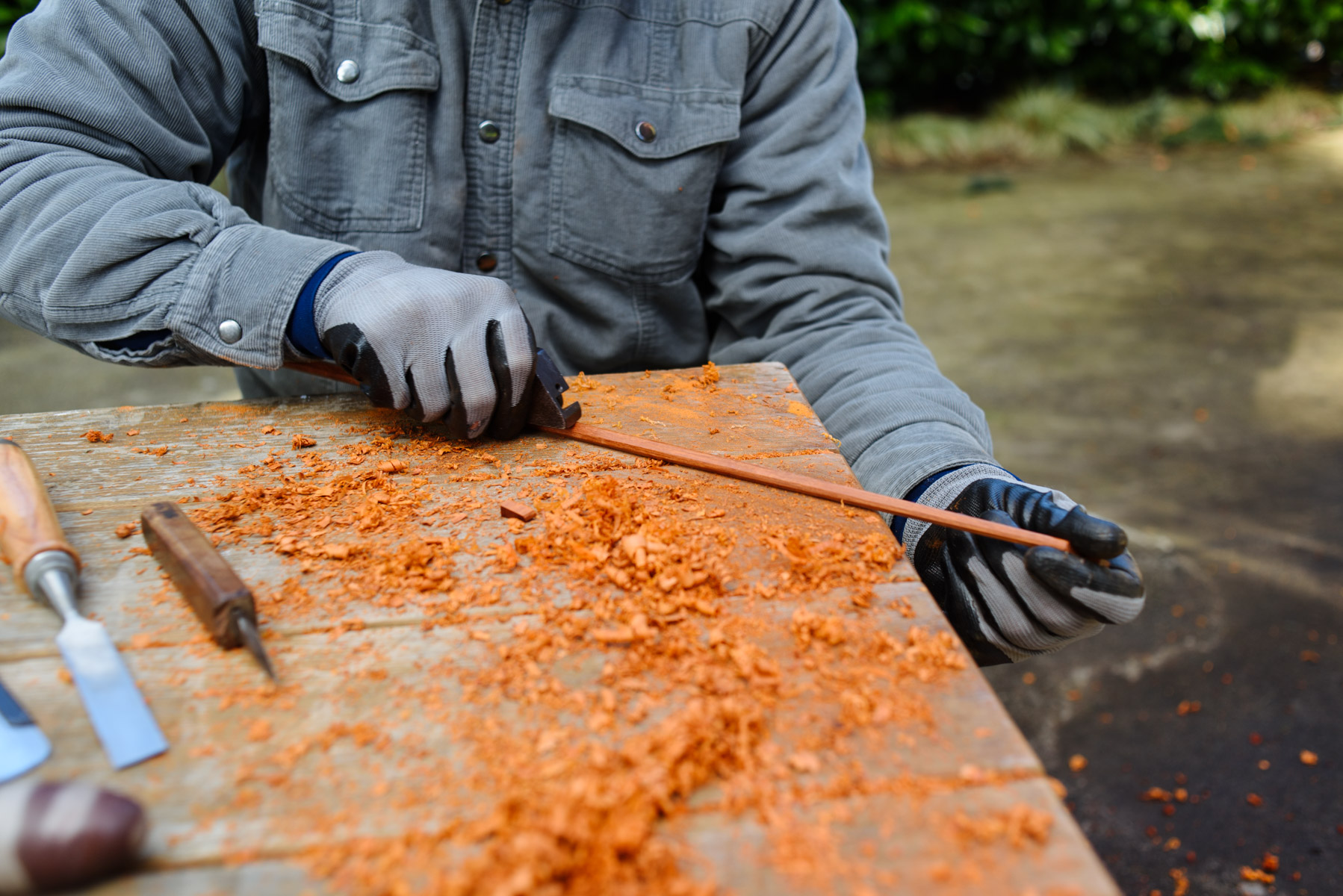 Roughing out the pernambuco stick with a scraper plane. If the weather is nice Jacob prefers to work with pernambuco outside to avoid breathing the irritable orange resinous dust
