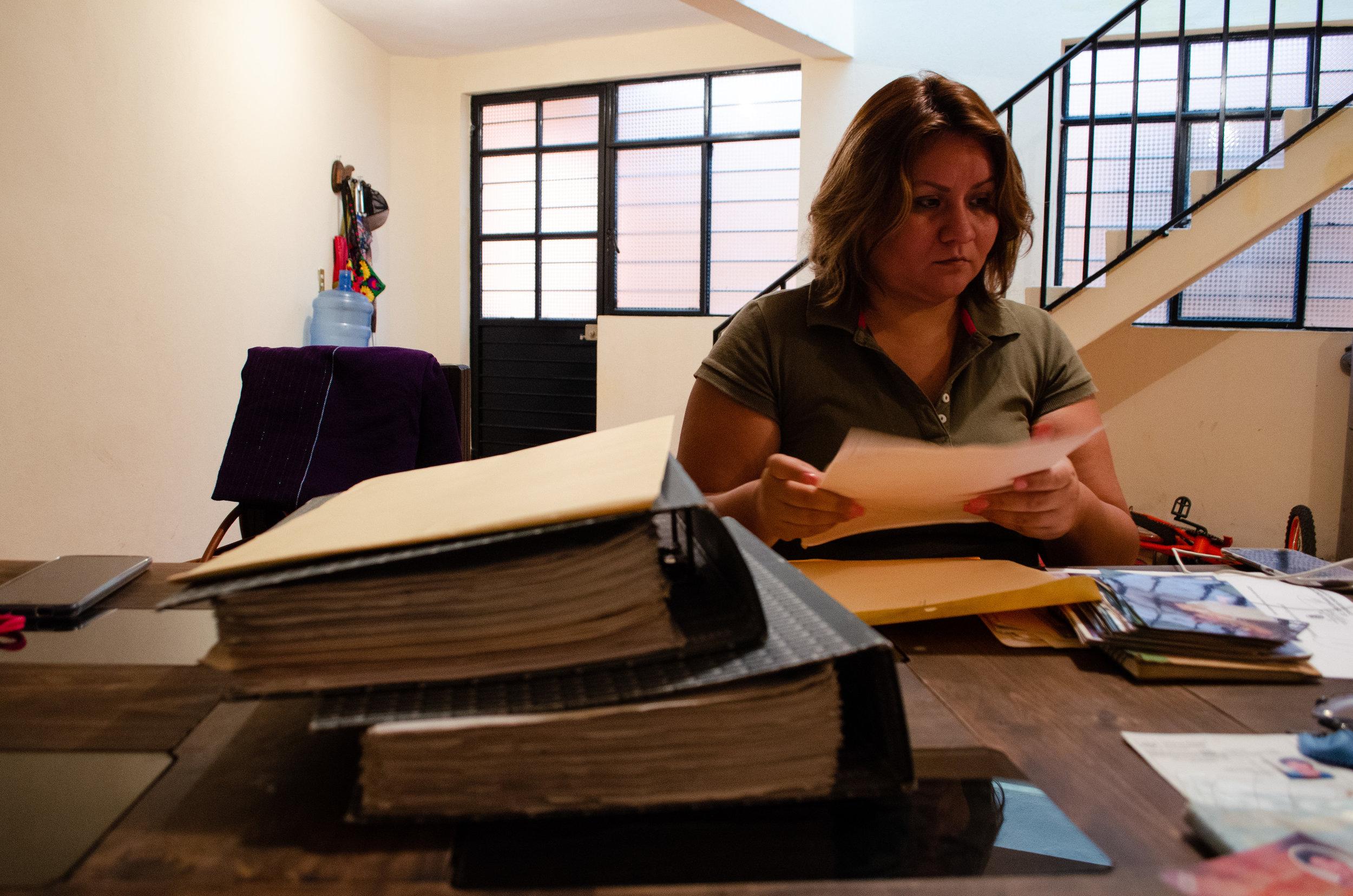 Yamil Trejo, madre de Yuri, revisando los expedientes de las averiguaciones del caso de Yuri.
