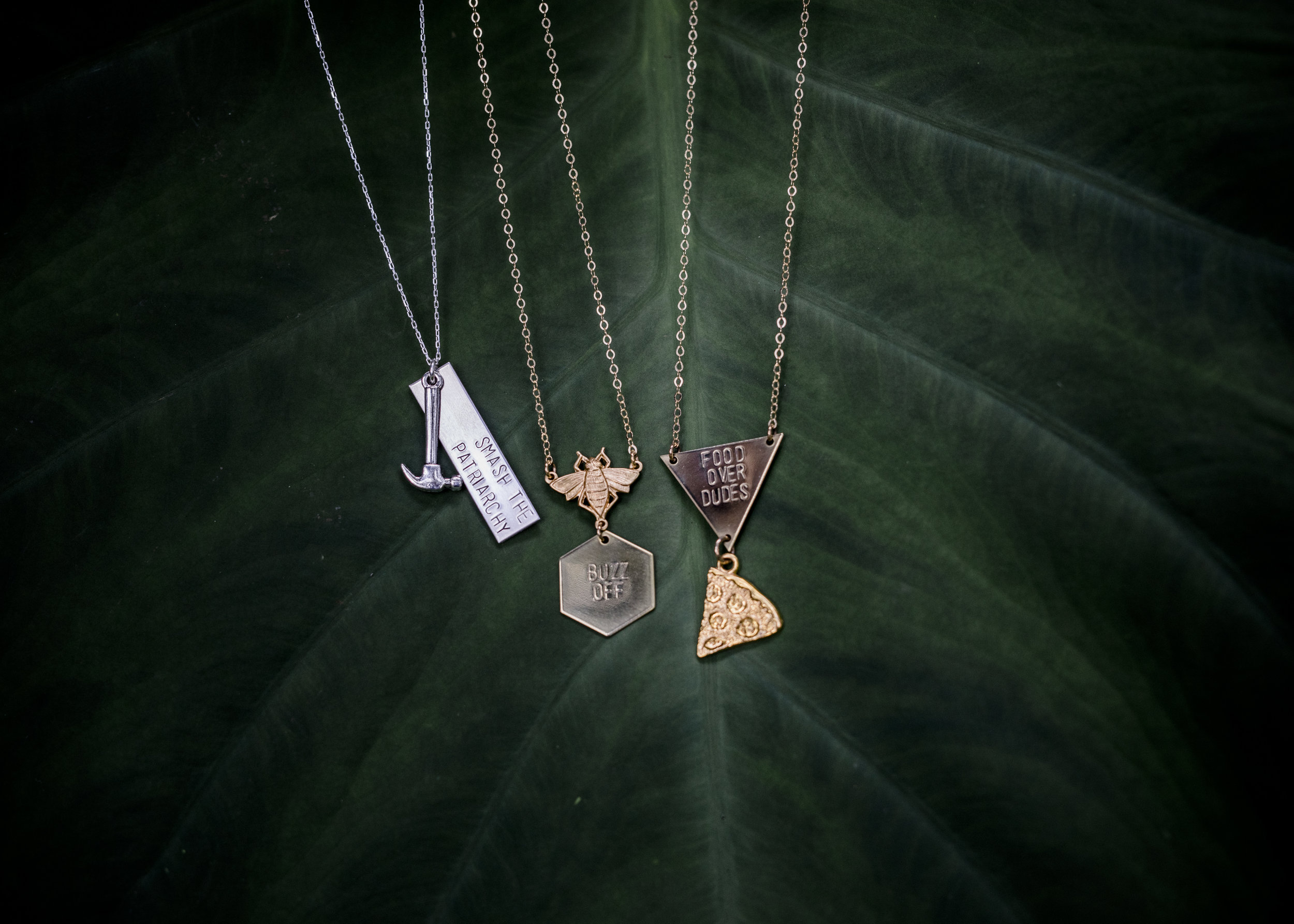 Smash the Patriarchy, Buzz Off, Food Over Dudes... a few necklaces by Arkansas jewelry maker Stacey Bowers of Bang-Up Betty jewelry.