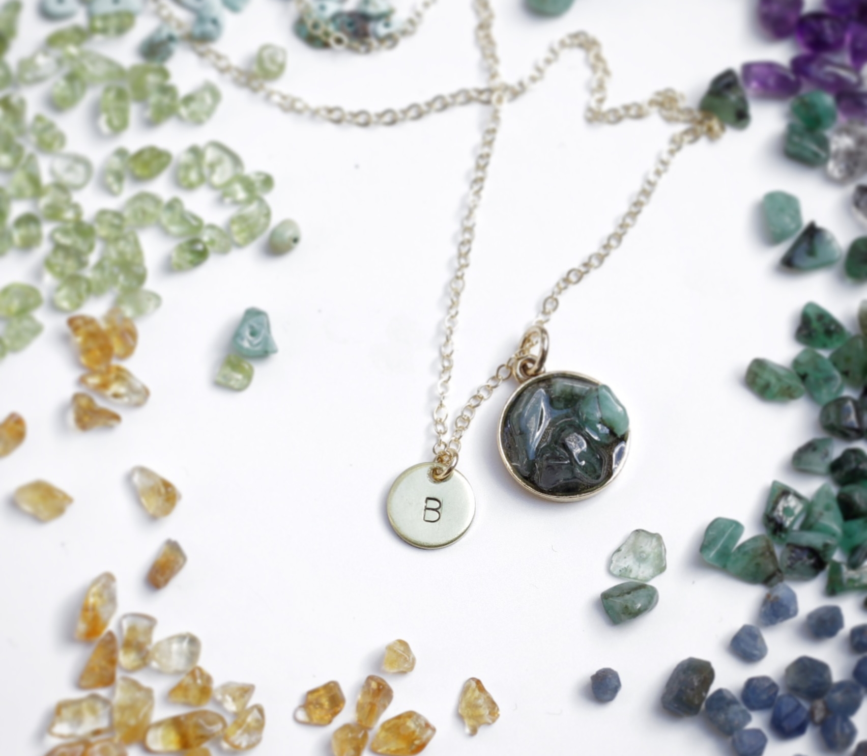 A custom natural emerald  cluster birthstone necklace , set in resin and surrounded by natural gemstones, including sapphire, amethyst, peridot, turquoise and citrine. Natural gemstones are the focus of Bang-Up Betty's new collection of handmade birthstone jewelry.