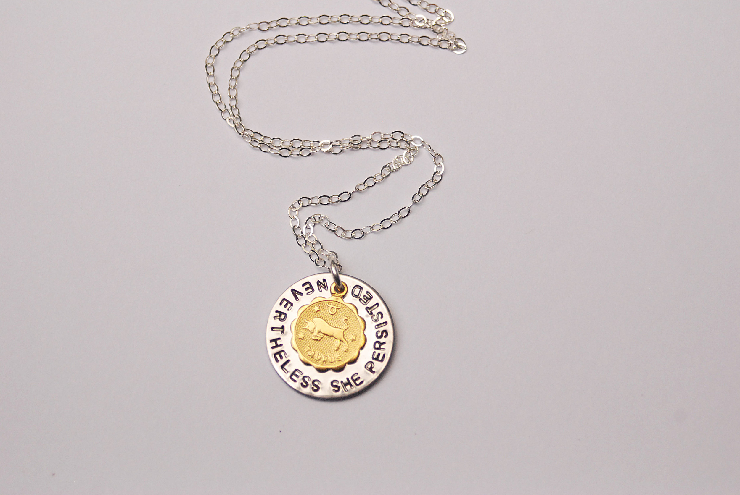 "This Taurus zodiac necklace was made for the strong-willed, stubborn, ambitious Tauruses out there. It reads ""Nevertheless She Persisted.""  Click here  to see the entire zodiac necklace collection."
