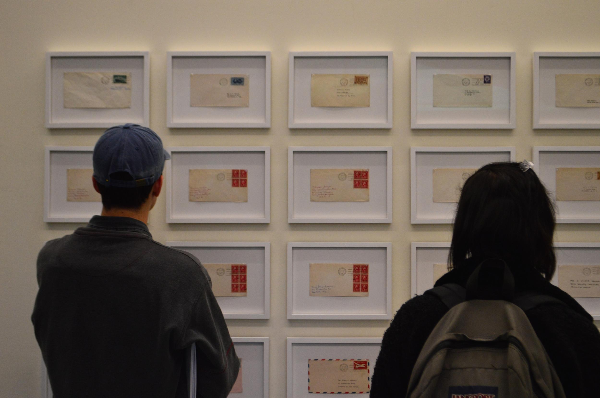 """""""Students gaze at handwritten postcards through glass"""""""